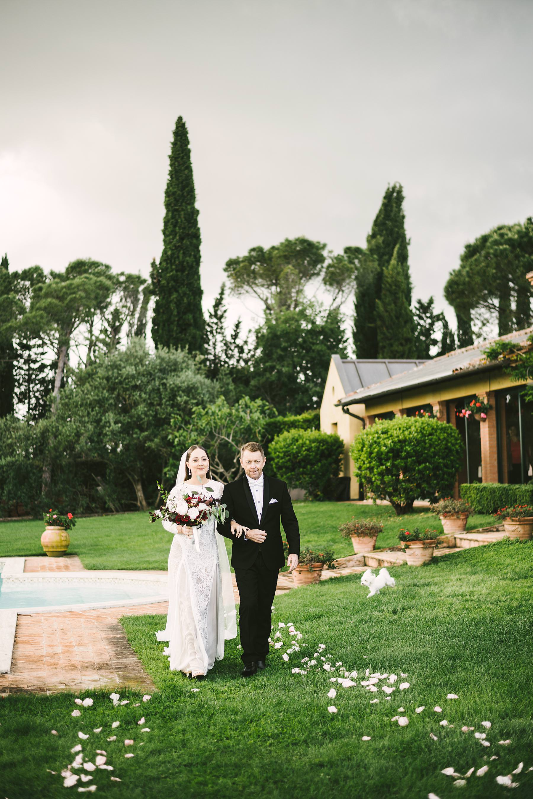 Bride Holly in Grace Loves Lace wedding dress walks down the aisle with her father in intimate destination wedding in Umbria at incredible historic venue Villa l'Antica Posta