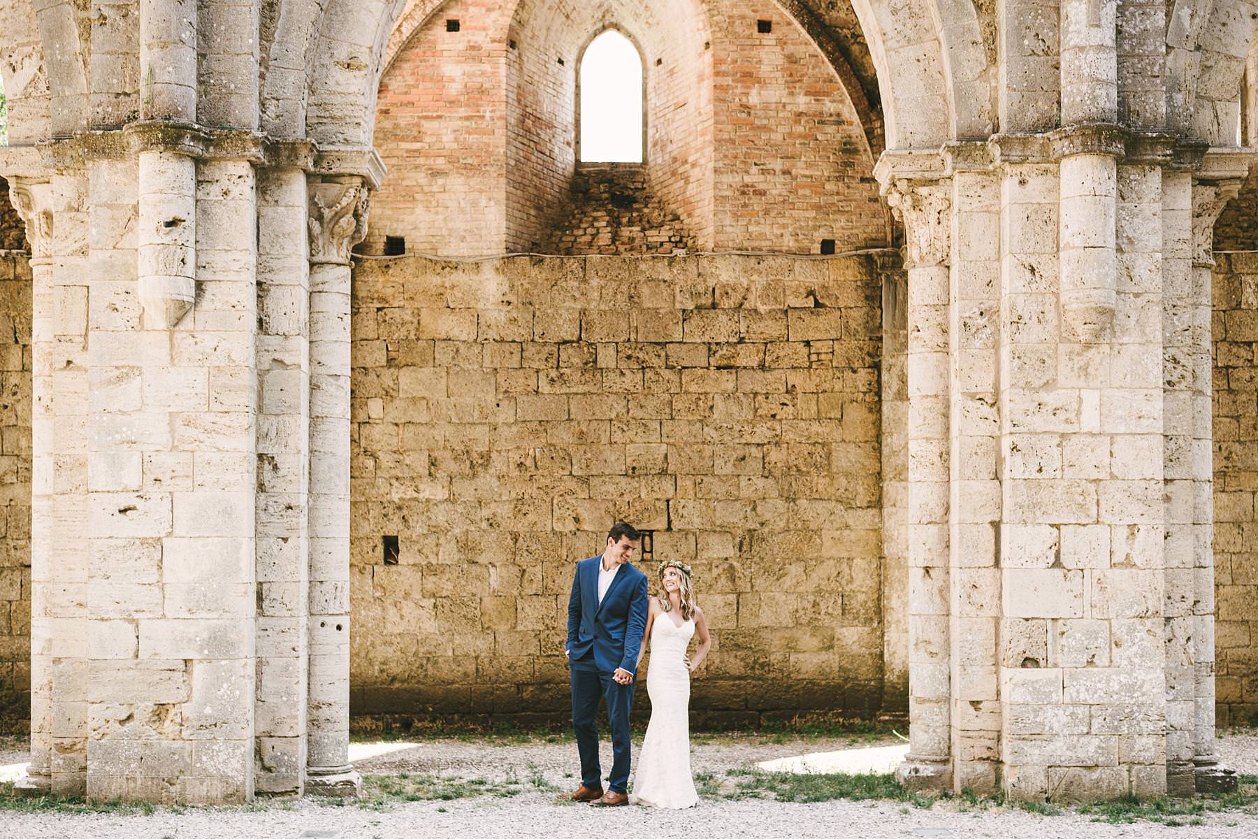 Lovely bride and groom portraiture session with colours, light, architecture and love gestures at Roofless Abbey of San Galgano. Italian civil destination wedding in Tuscany