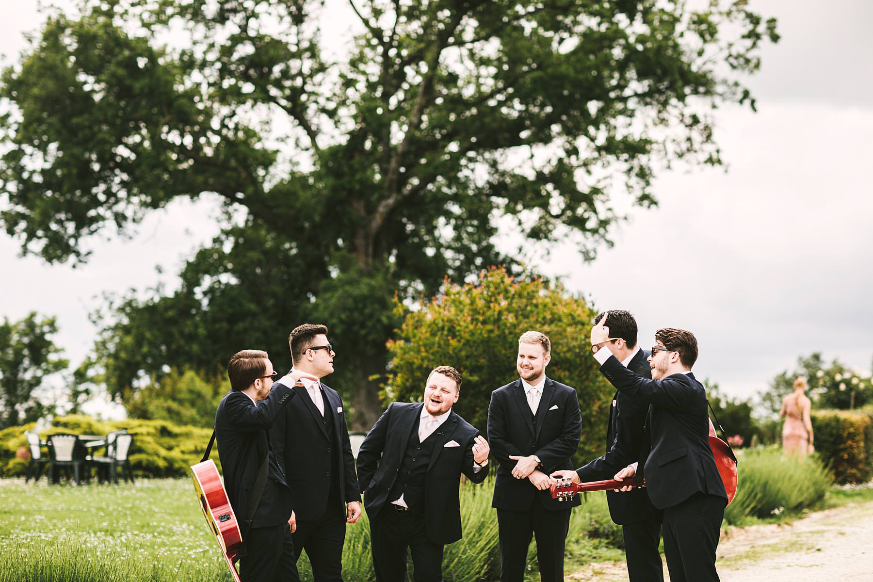 Groom and mens exciting photo shoot just before the outdoor intimate destination wedding ceremony in Tuscany countryside venue of Villa Le Bolli near Radicondoli