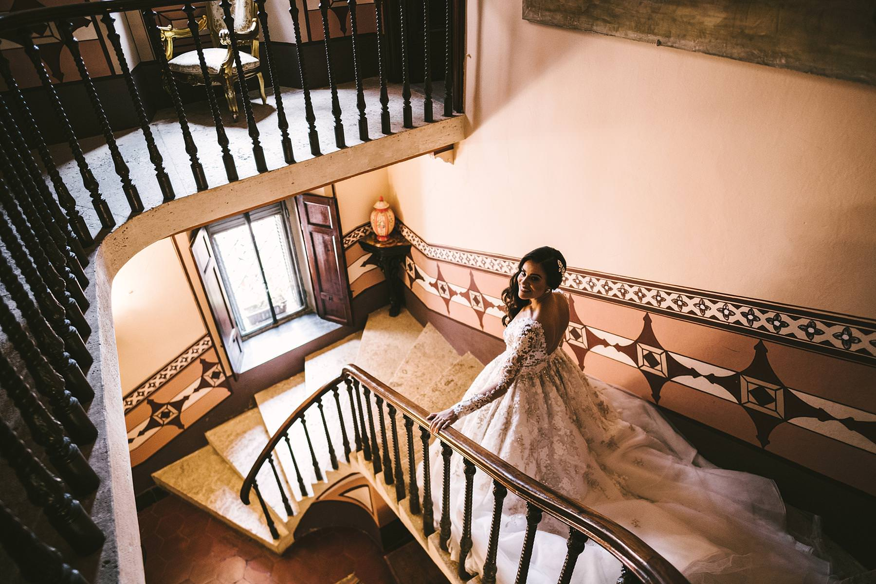 Rippling and sumptuous Tuscany wedding in the elegant Castle of Valenzano. Gorgeous bride Ilyssa in Ysa Makino elegant dress walks down the staircase of the castle