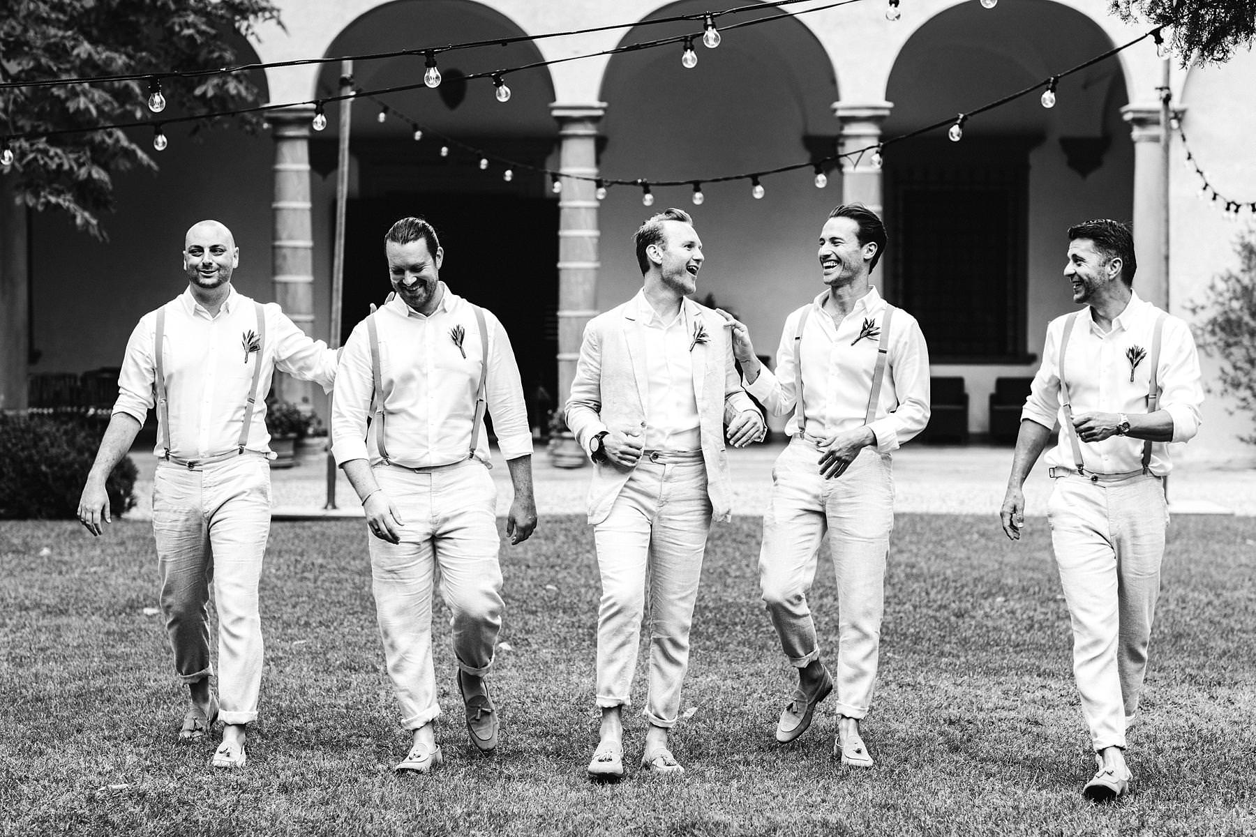 Coll groom with groomsmen walk just before the outdoor ceremony in the olive groves in Chianti at the historical residence of Villa Il Poggiale