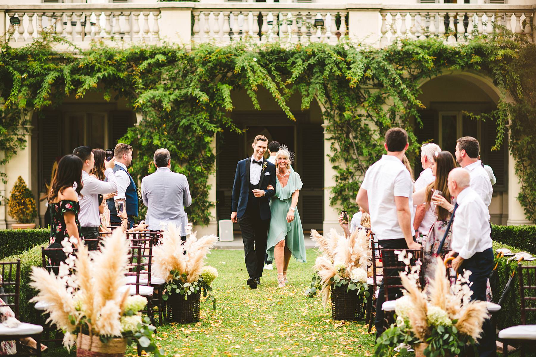 Groom Cheyne walks down the aisle with mom. Intimate destination wedding ceremony in Florence at Villa La Vedetta