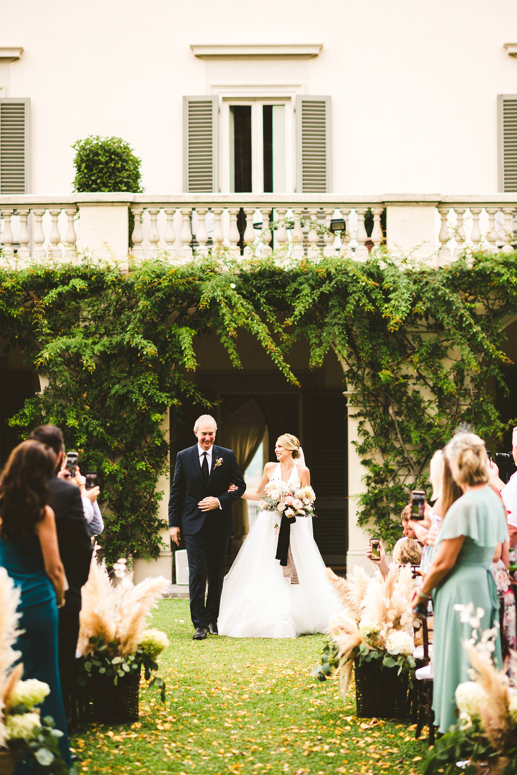 Bride Christina just walks down the aisle in the elegant garden and ceremony decor at Villa La Vedetta, Florence. Luxury destination wedding in Florence