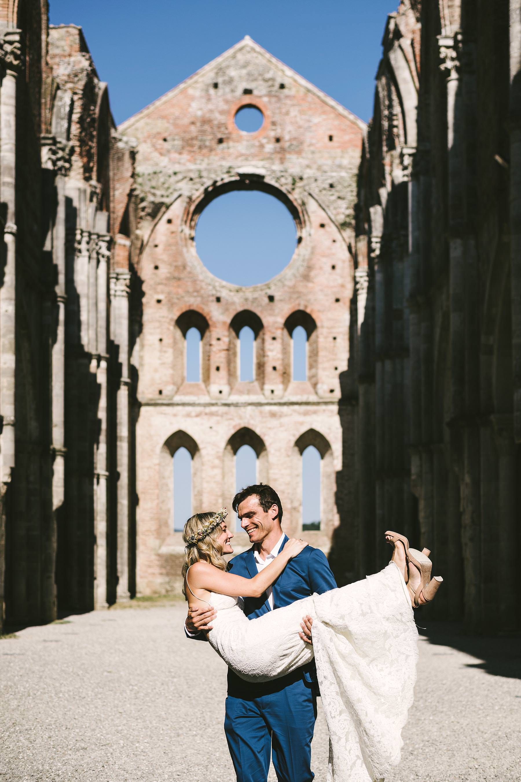 Unforgettable bride and groom wedding portrait at the Roofless Abbey of San Galgano full of colours, light, architecture and love gestures. Intimate destination Italian civil wedding in Tuscany