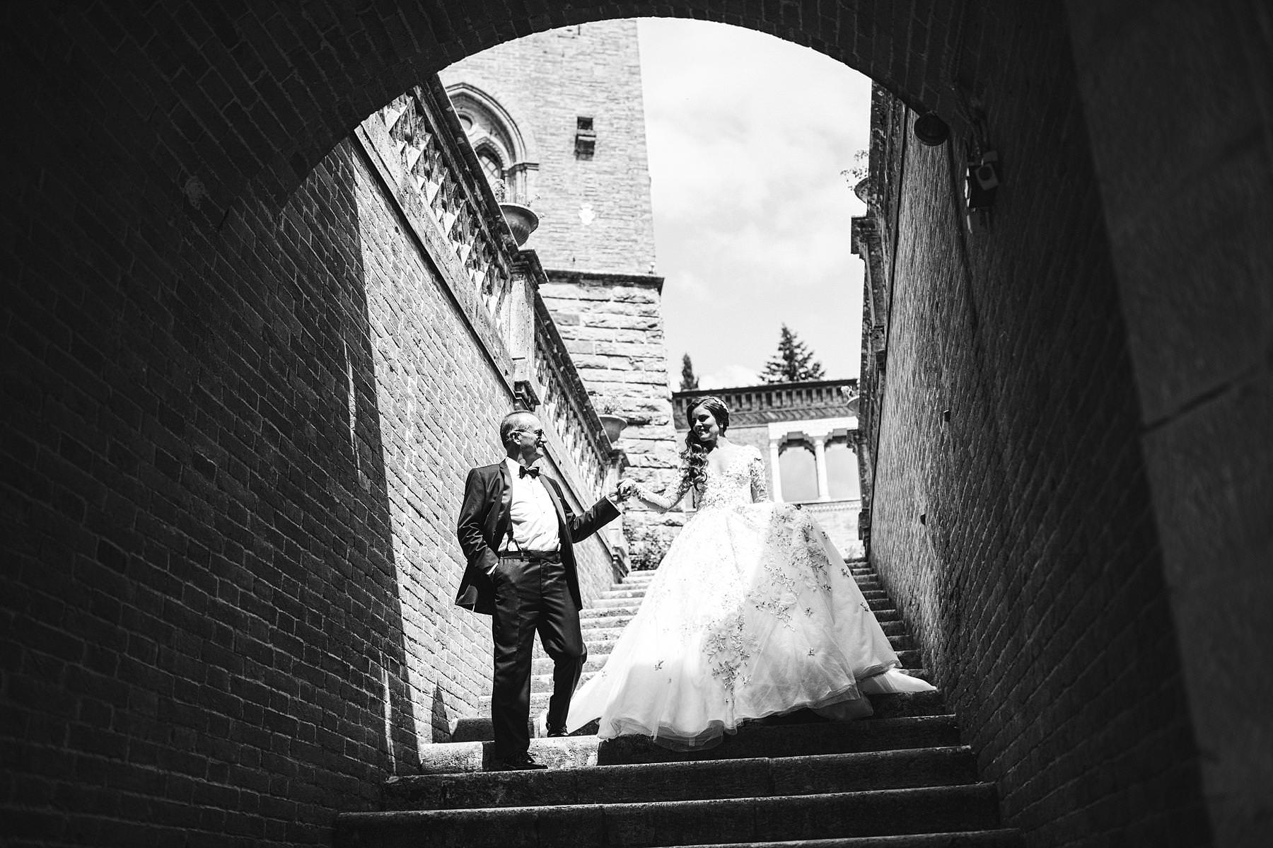 Bride in Ysa Makino wedding gown walks with father in the Valenzano Castle historic staircase
