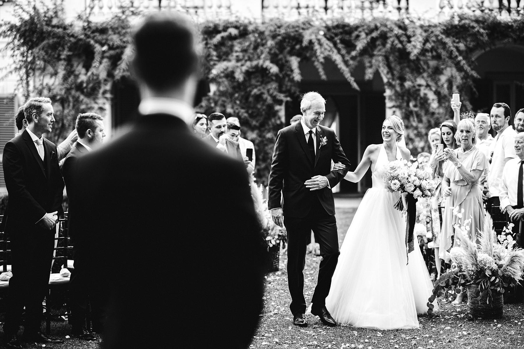 Lovely bride Christina in her Liancarlo wedding dress walks down the aisle with dad in the elegant garden and ceremony decor at Villa La Vedetta, Florence. Luxury destination wedding in Florence