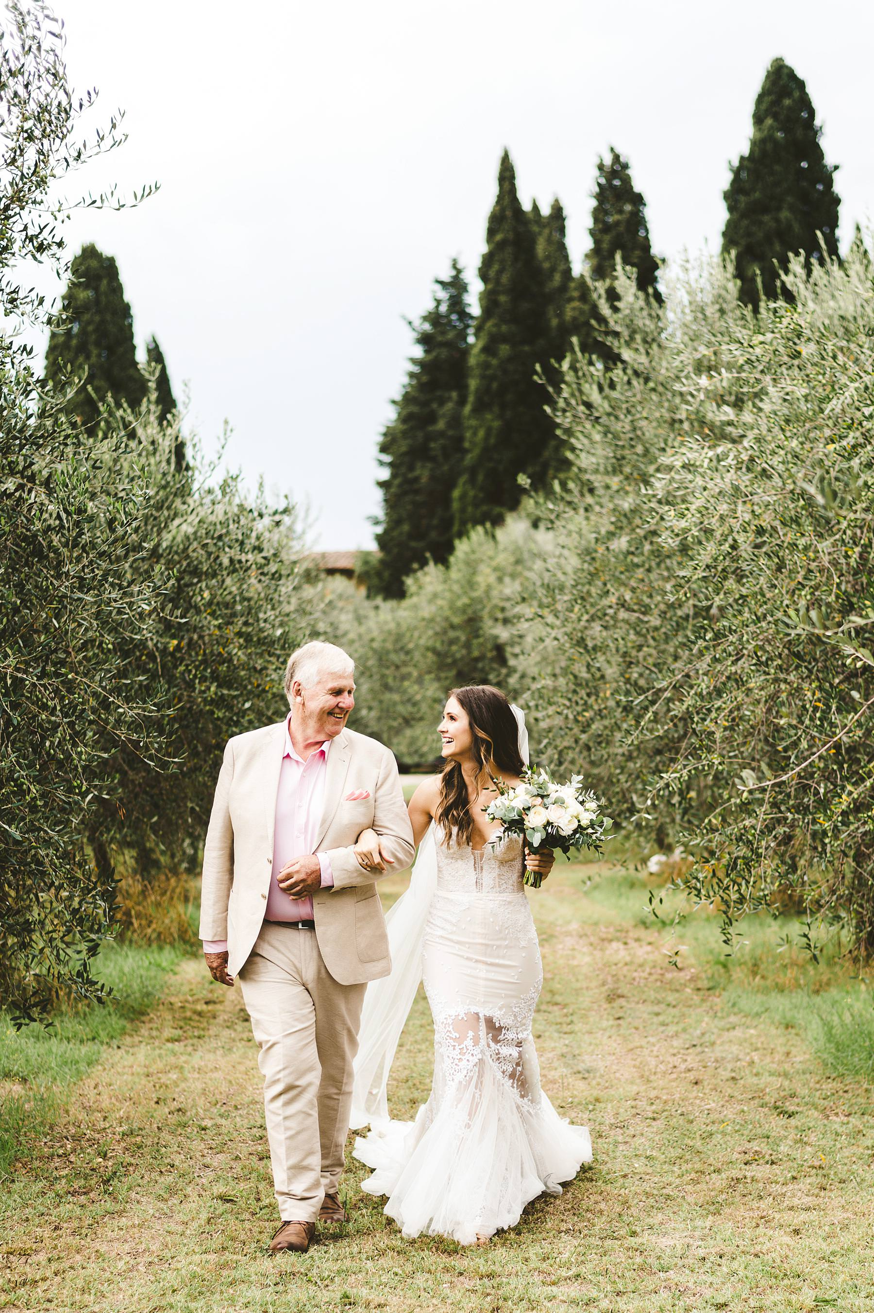 Lovely bride walks down the aisle in the middle of Olive groves of the historical residence of Villa Il Poggiale in the countryside of Chianti