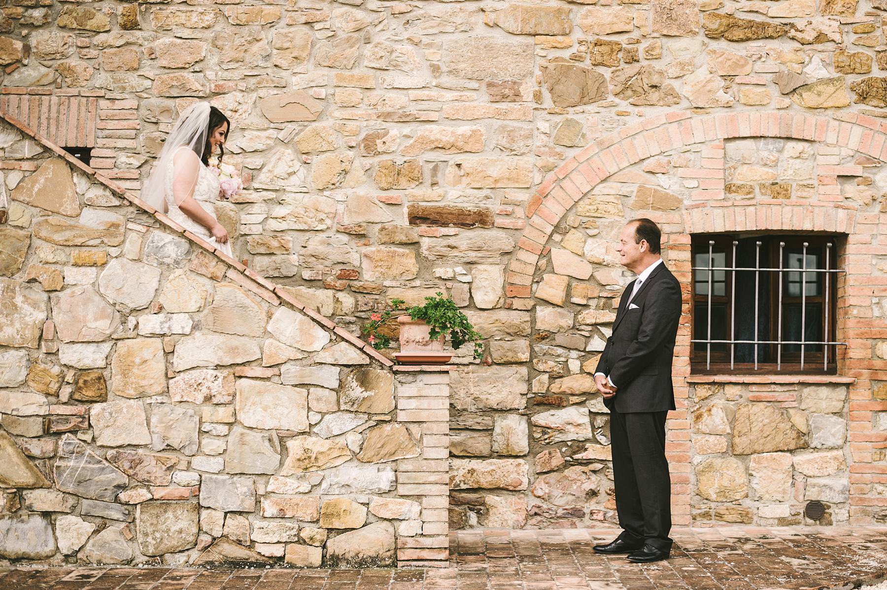 Lovely and emotional symbolic outdoor wedding ceremony at Villa Le Bolli venue near Radicondoli. Bride Hillary sees her father just before to walks down the aisle