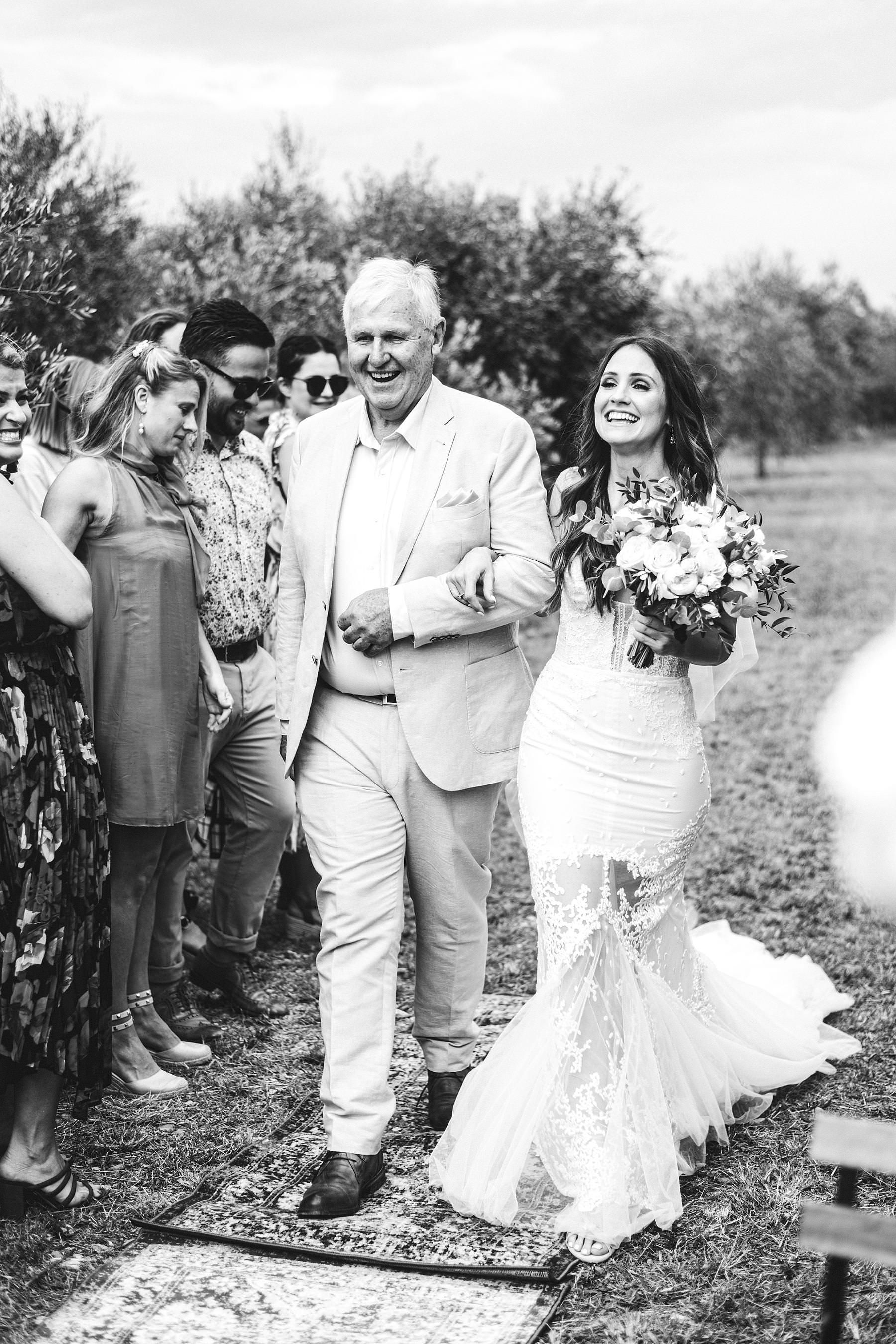 Emotional bride walks down the aisle in the middle of Olive groves of the historical residence of Villa Il Poggiale in the countryside of Chianti