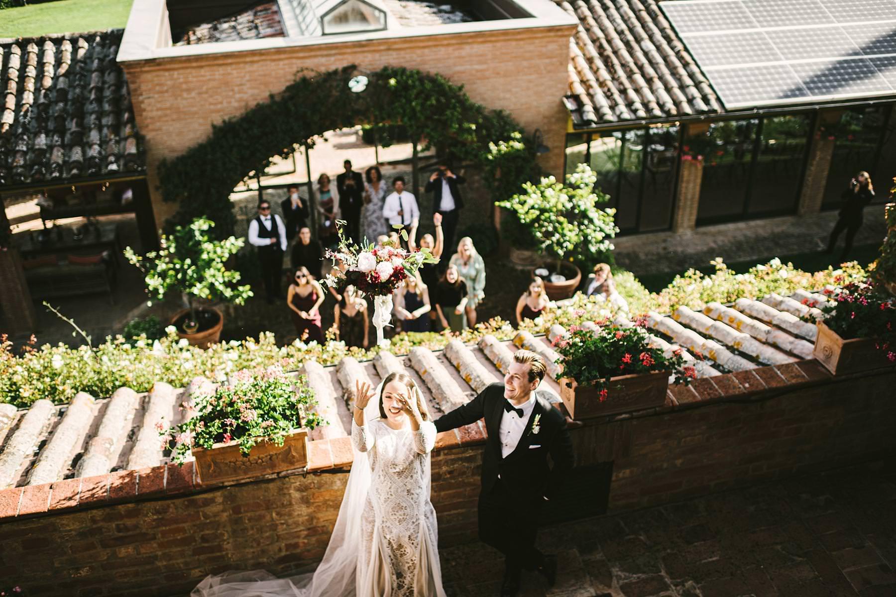 Exciting fun and elegant intimate destination wedding in Umbria at historic incredible venue Villa l'Antica Posta. Bridal bouquet toss