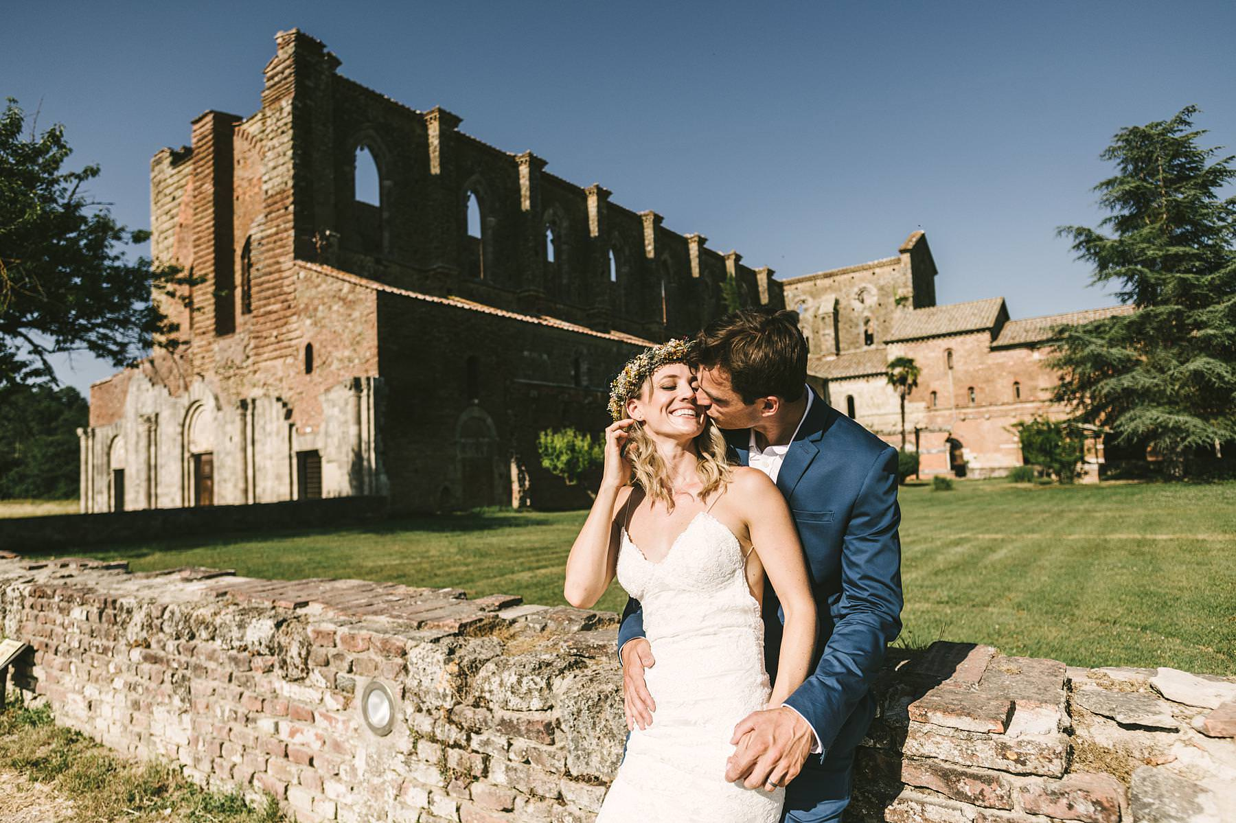 Lovely bride and groom wedding portrait at the Roofless Abbey of San Galgano full of colours, light, architecture and love gestures. Intimate destination Italian civil wedding in Tuscany