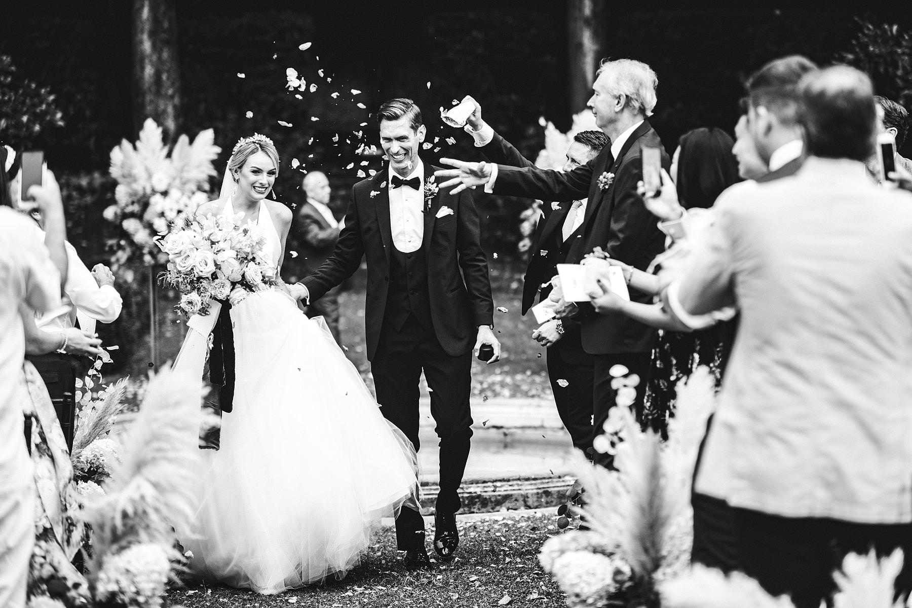 Happiness for bride and groom just married in Florence at Villa La Vedetta. Romantic and timeless wedding photo during petal throwing at the end of the outdoor intimate ceremony hosted in the Italian garden of the Villa
