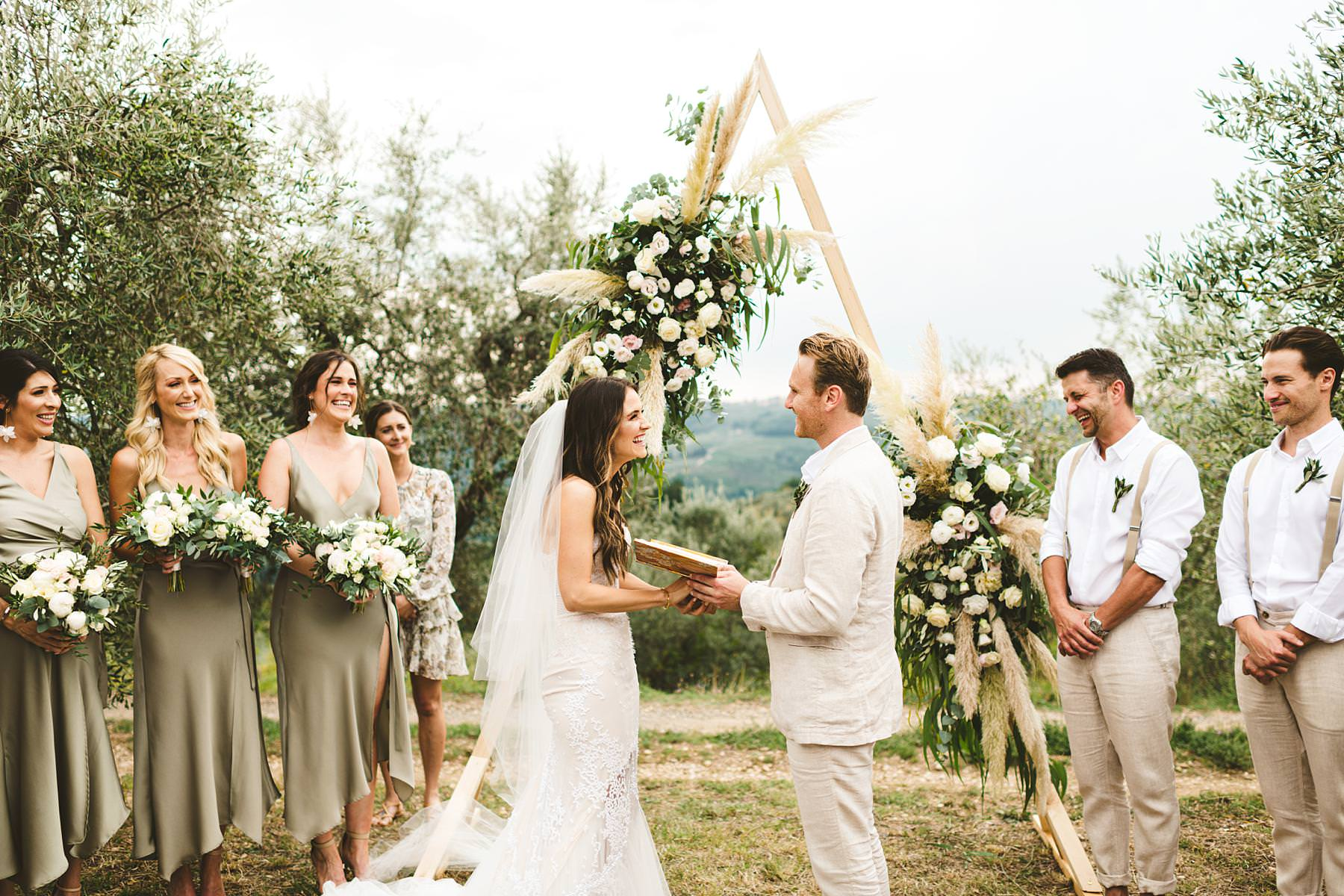 Lovely outdoor symbolic wedding ceremony decor with triangular shape as a stunning frame that witnessed bride and groom promises of love. Modern and unusual wedding framed by the olive groves of Chianti