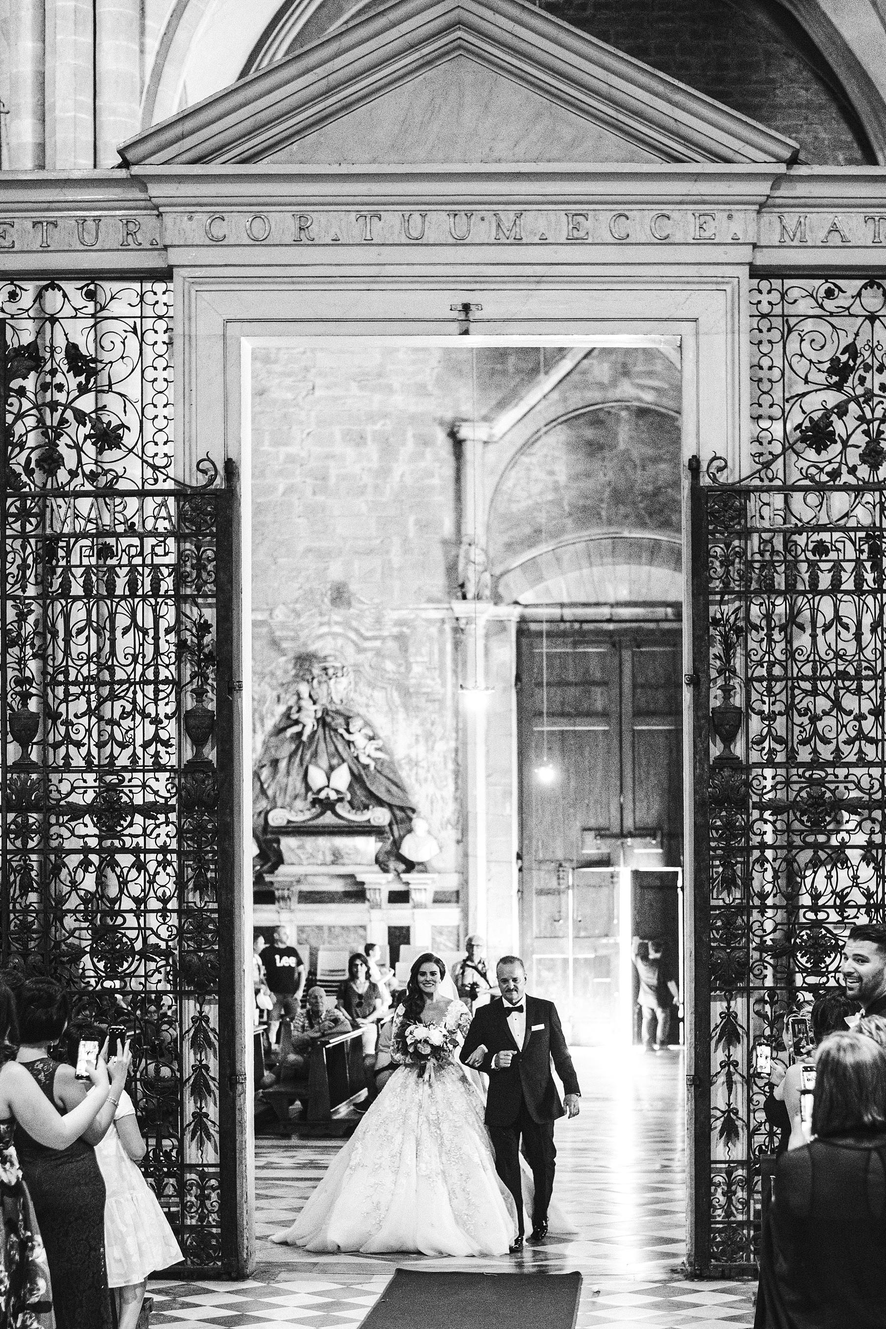 Beautiful bride Ilyssa in her Ysa Makino wedding gown walks down the aisle of Arezzo Cathedral with Father. Elegant destination castle wedding in Tuscany