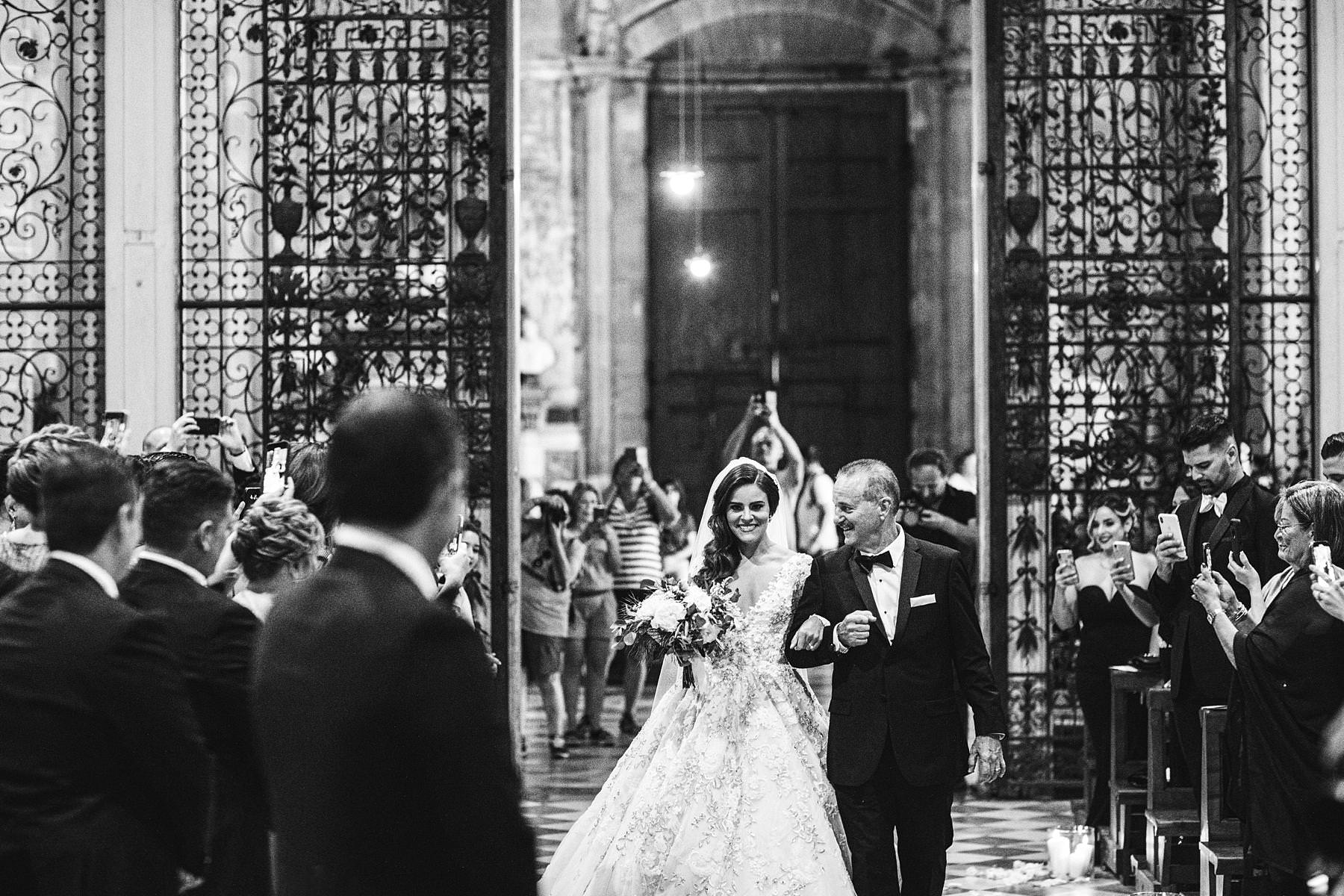 Beautiful bride Ilyssa in her Ysa Makino wedding gown walks down the aisle of Arezzo Cathedral with Father see for the first time the groom Alex. Elegant destination castle wedding in Tuscany with catholic ceremony in Arezzo