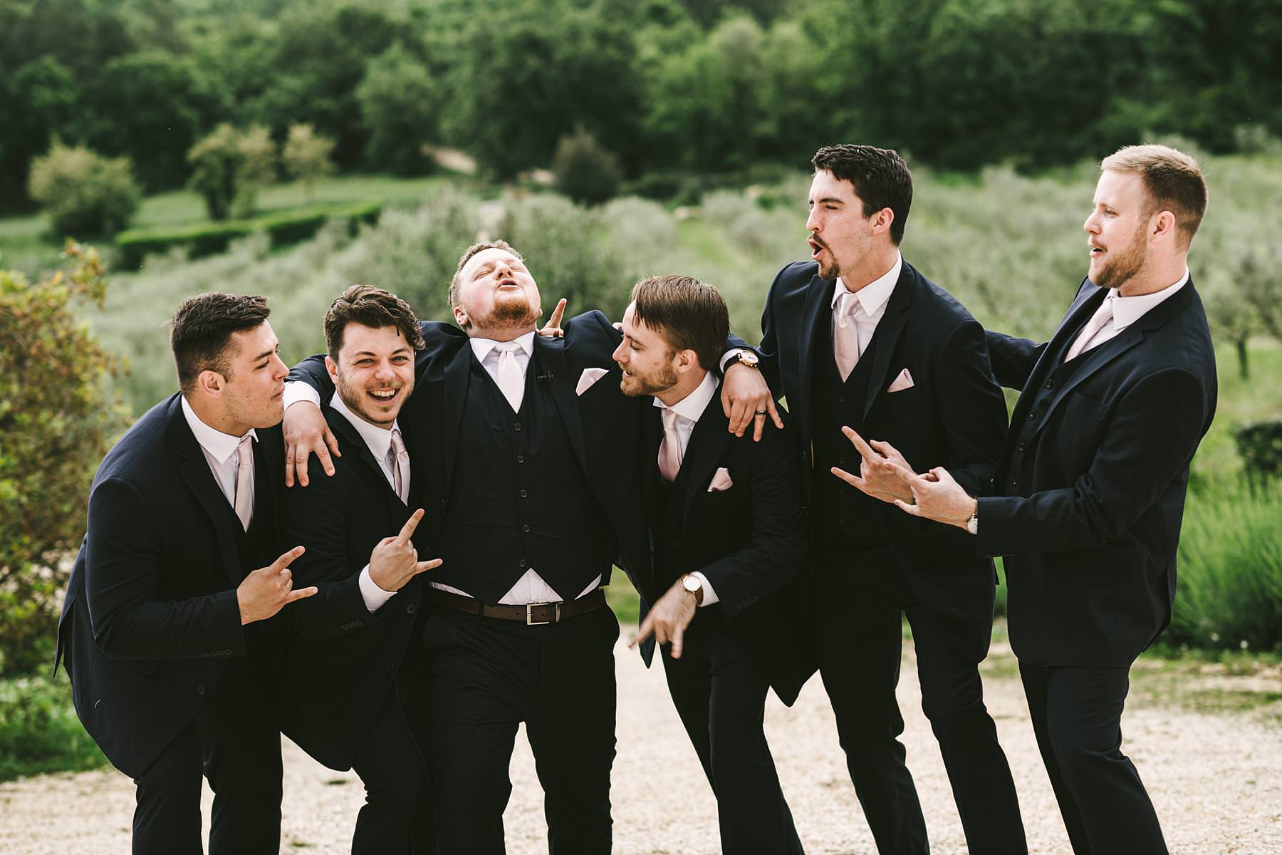 Exciting and fun cocktail wedding photo of the groom and the mens at intimate destination wedding in Tuscany at Villa Le Bolli
