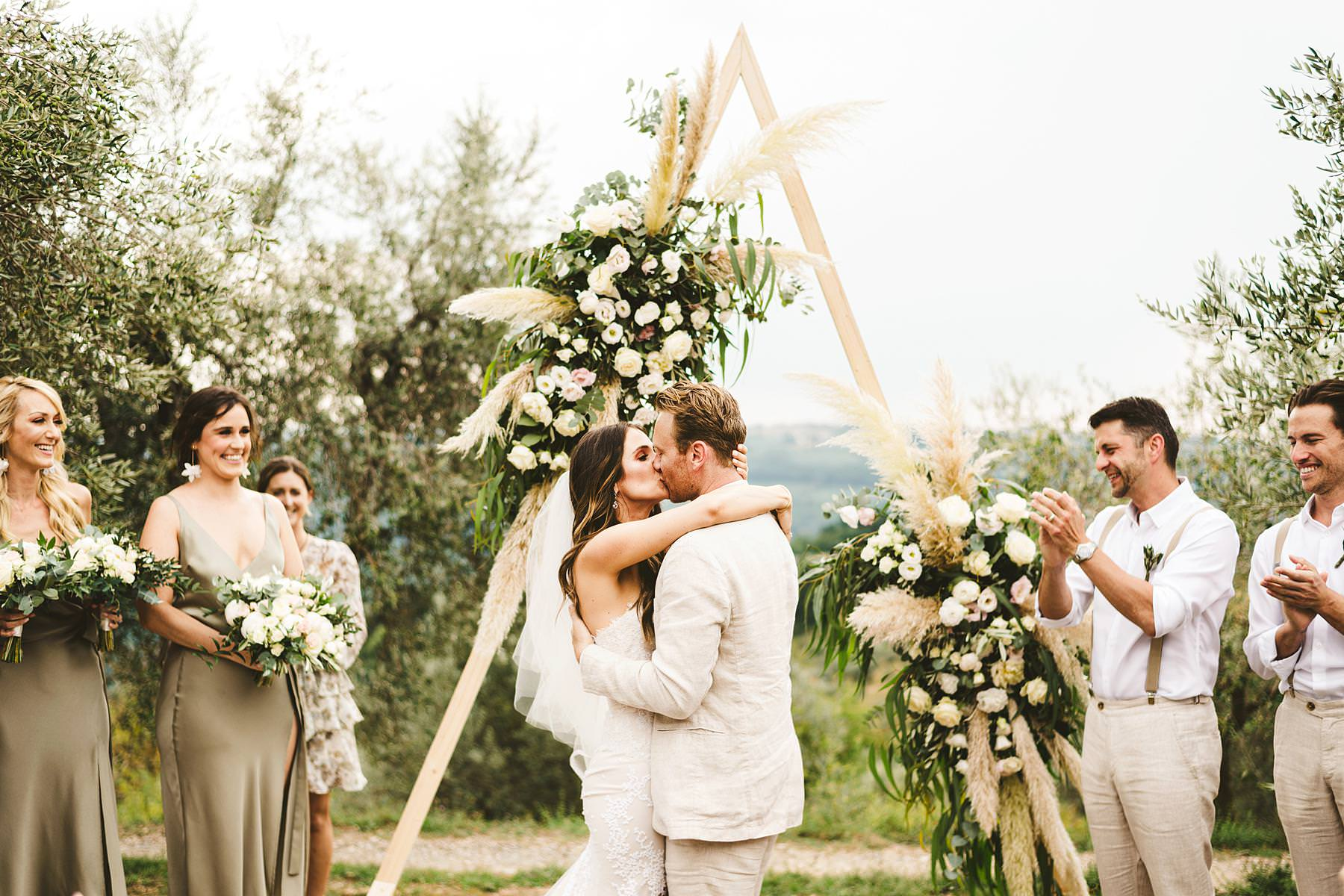 Lovely bride and groom first kiss framed by the olive groves of Chianti at the historic residence of Villa Il Poggiale in the countryside of Chianti
