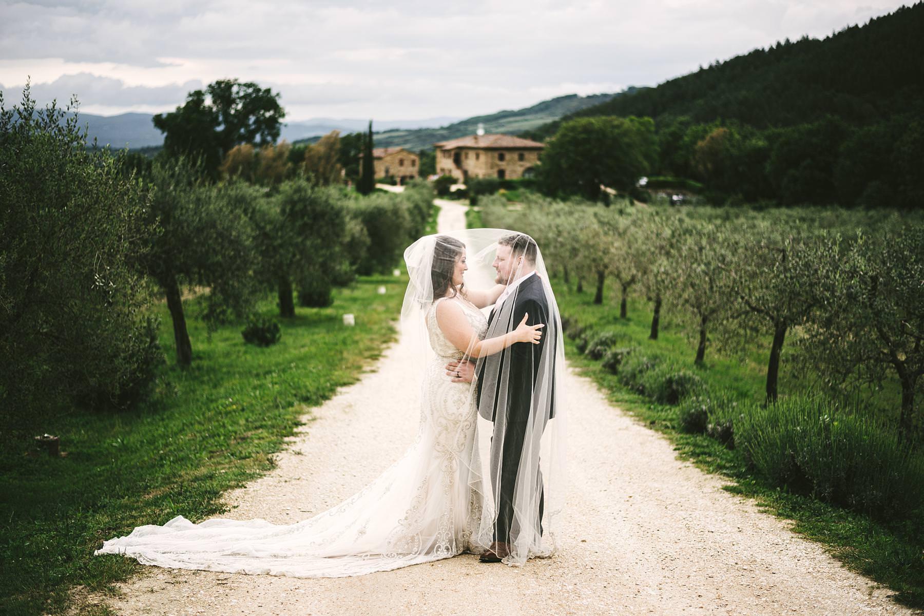 Beautiful bride and groom wedding photo in the white street of Villa Le Bolli venue near Radicondoli