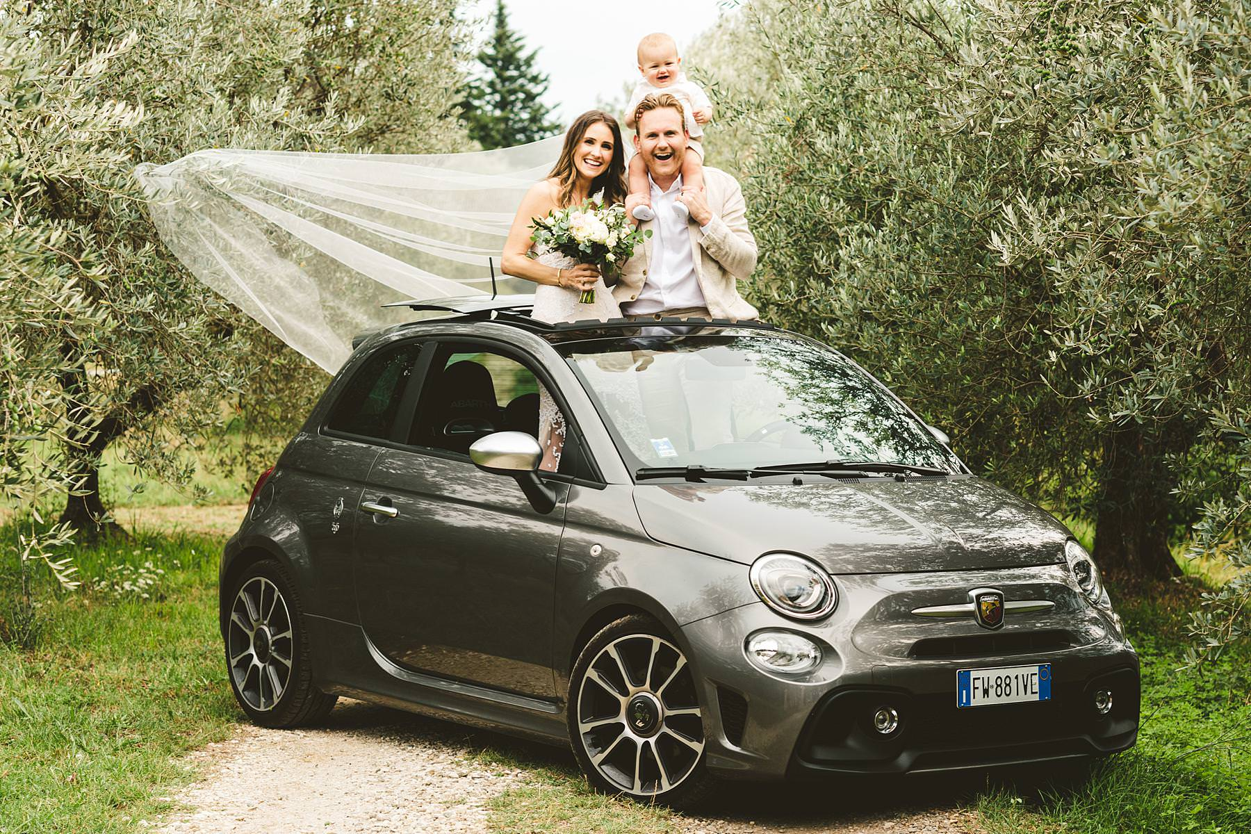 Bride and groom portrait with Fiat500 Abarth in the olive groves of Chianti near the historic residence of Villa Il Poggiale