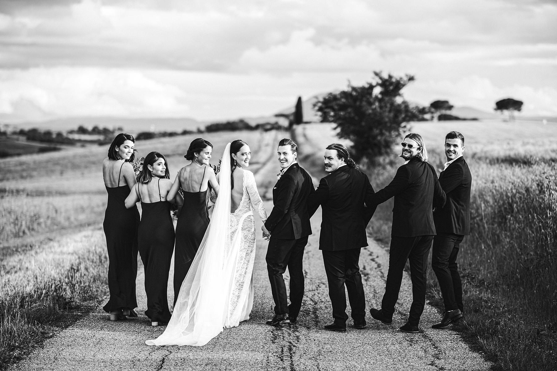 Exciting bridal party wedding photo in the countryside of Umbria with corn field as the background. Intimate destination symbolic wedding day at incredible historic venue Villa l'Antica Posta