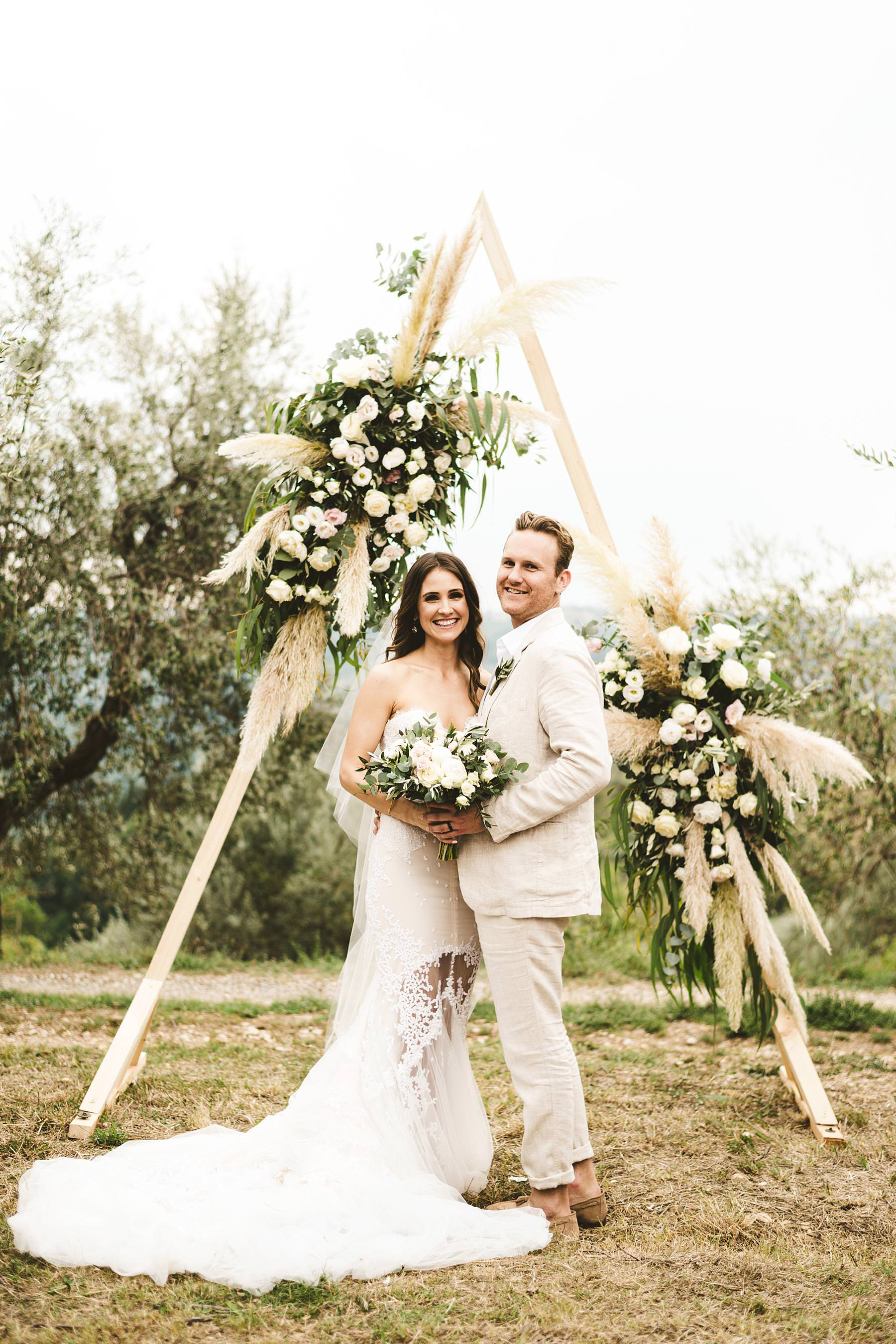Bride and groom portrait framed by a lovely triangular shape that witnessed their promises of love. Elegant and modern unusual wedding framed by the olive groves of Chianti