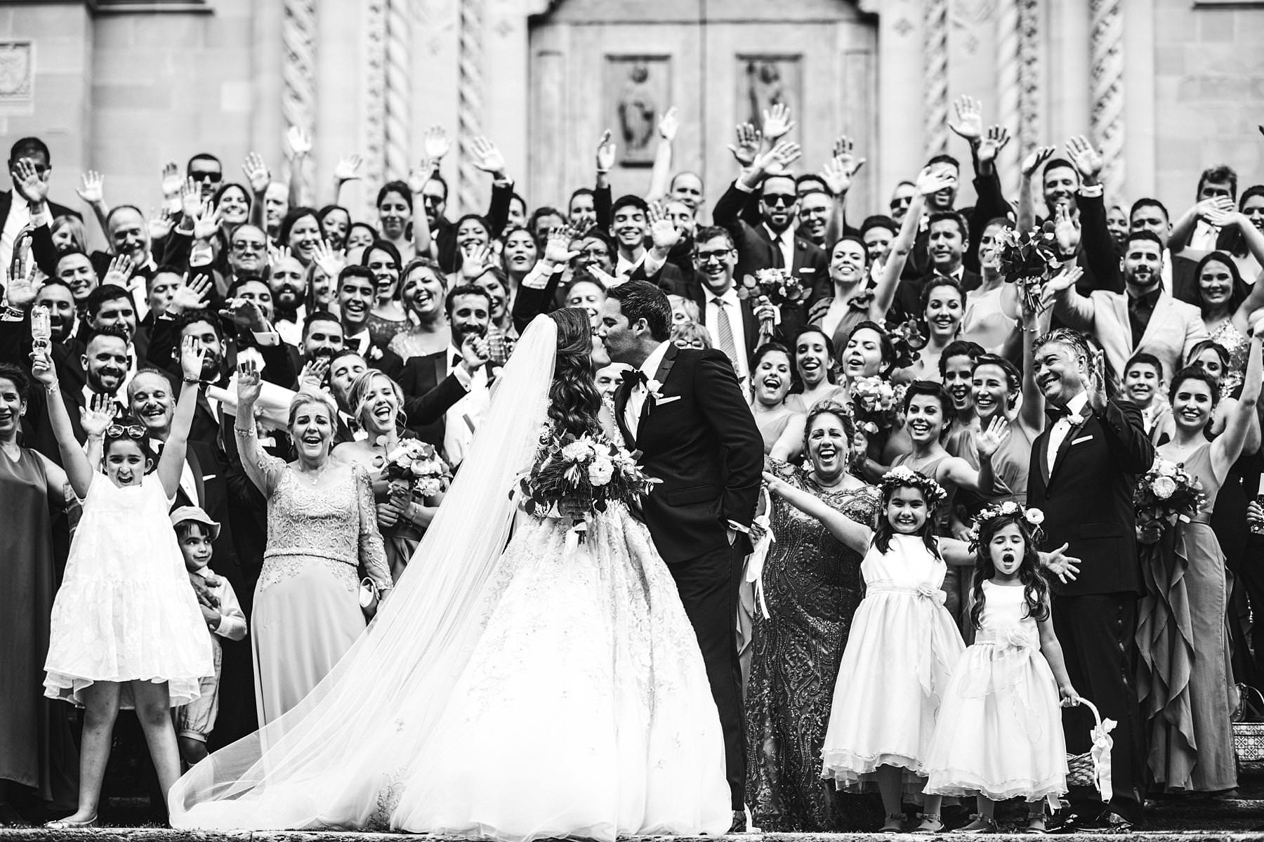 Rippling and sumptuous Tuscany wedding in the elegant Castle of Valenzano. Elegant and exciting bride and groom group photo at Arezzo Cathedral