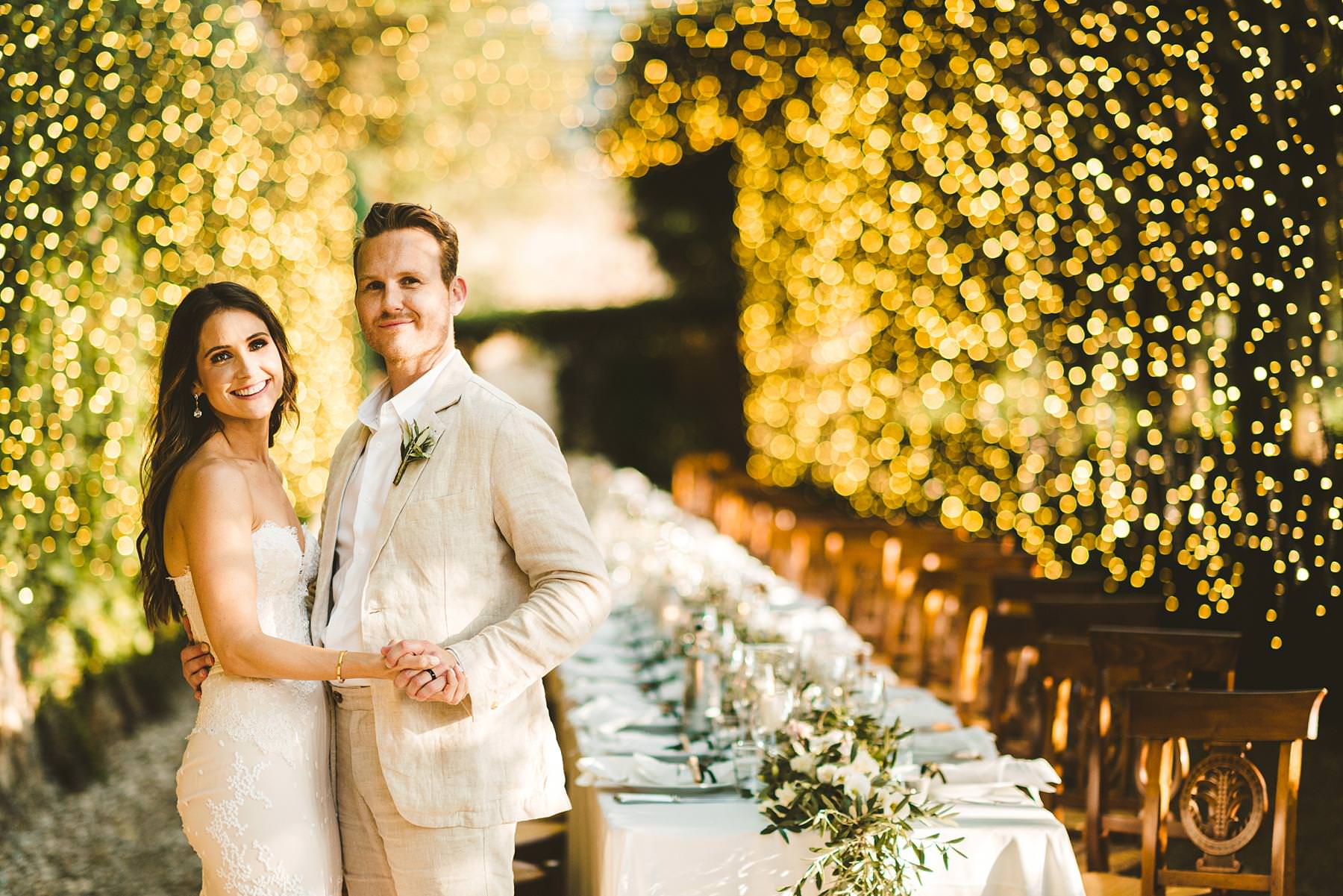 Lovely bride and groom portrait at the detailed tunnel of greenery and tiny, shining lights dinner decor at Villa Il Poggiale