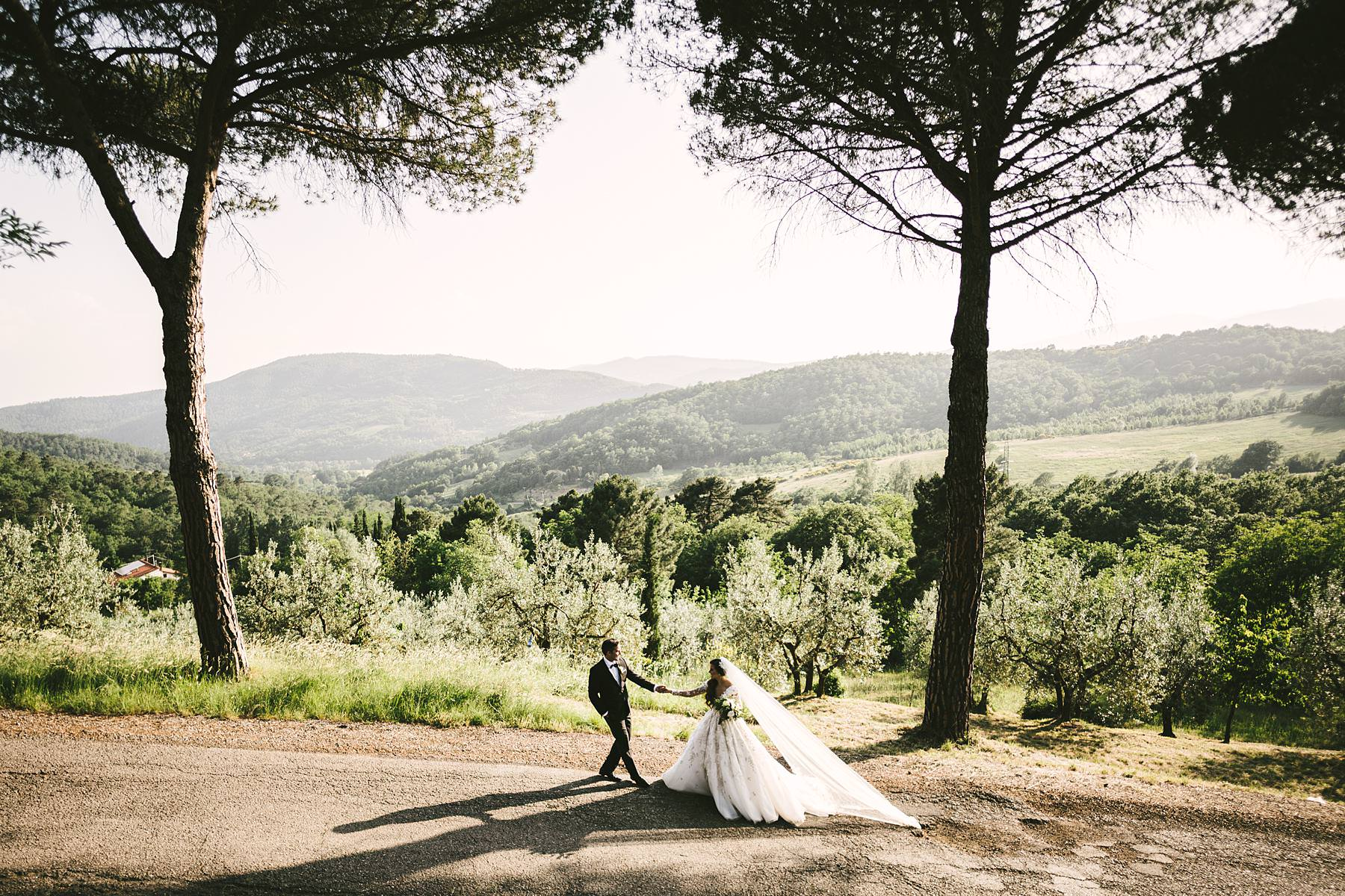 Rippling and sumptuous Tuscany countryside wedding in the elegant Castle of Valenzano. Unforgettable and romantic bride and groom portrait near Valenzano Castle. Castle destination wedding in Italy