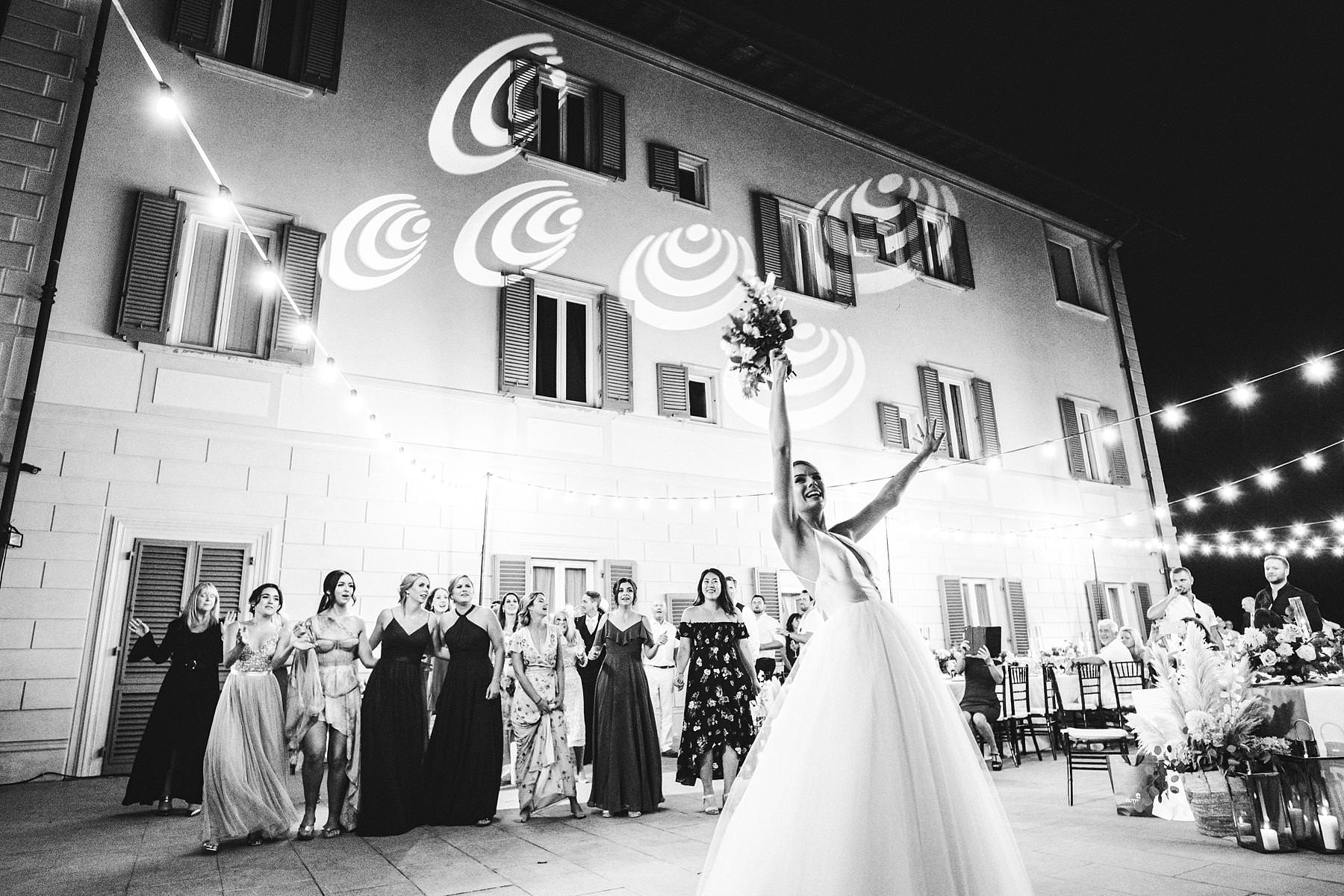 Exciting bridal bouquet toss at Villa La Vedetta in Florence. Intimate luxury wedding