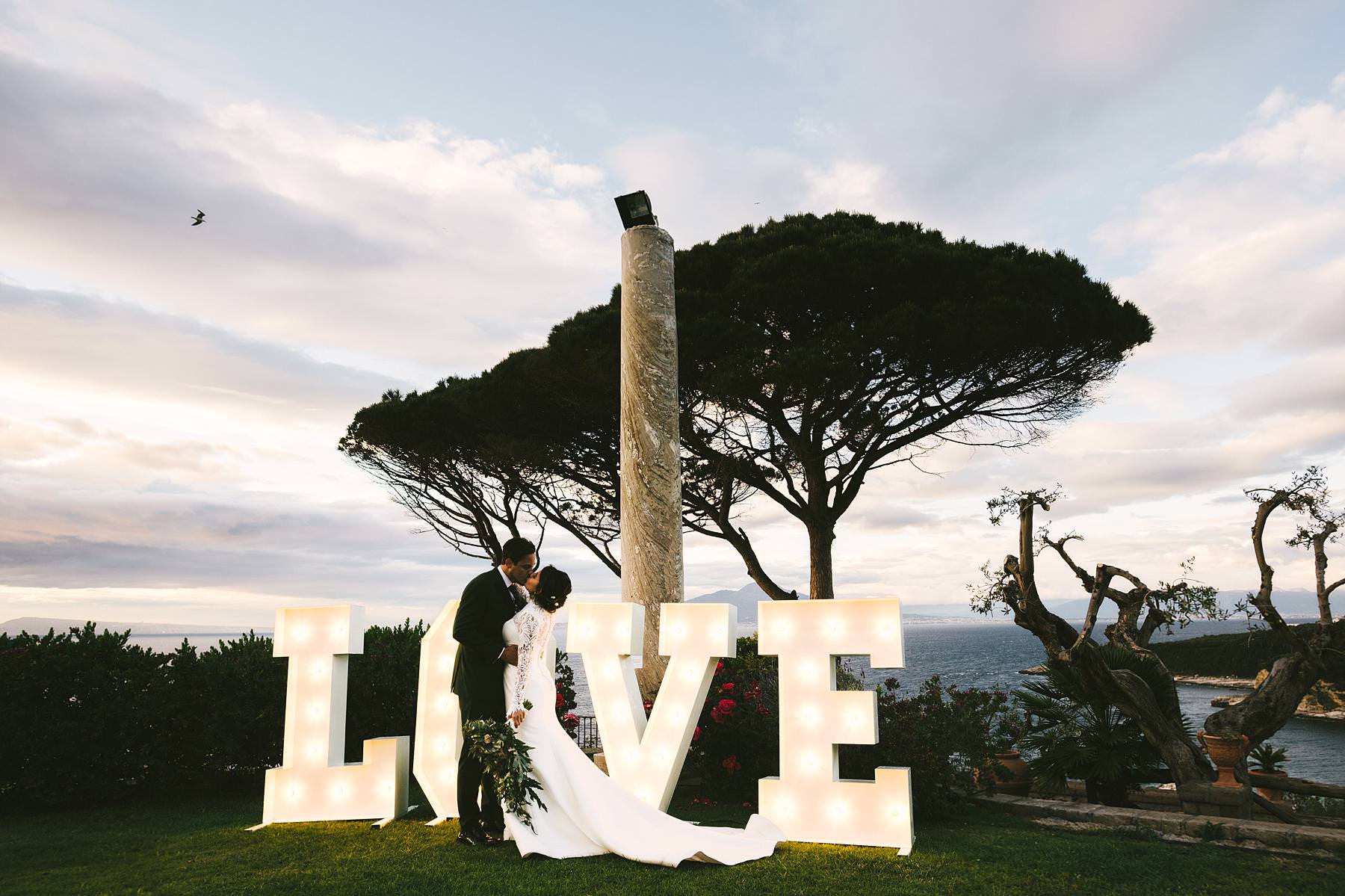 """Amazing bride and groom portrait with the """"love"""" sign at Villa Angelina venue"""