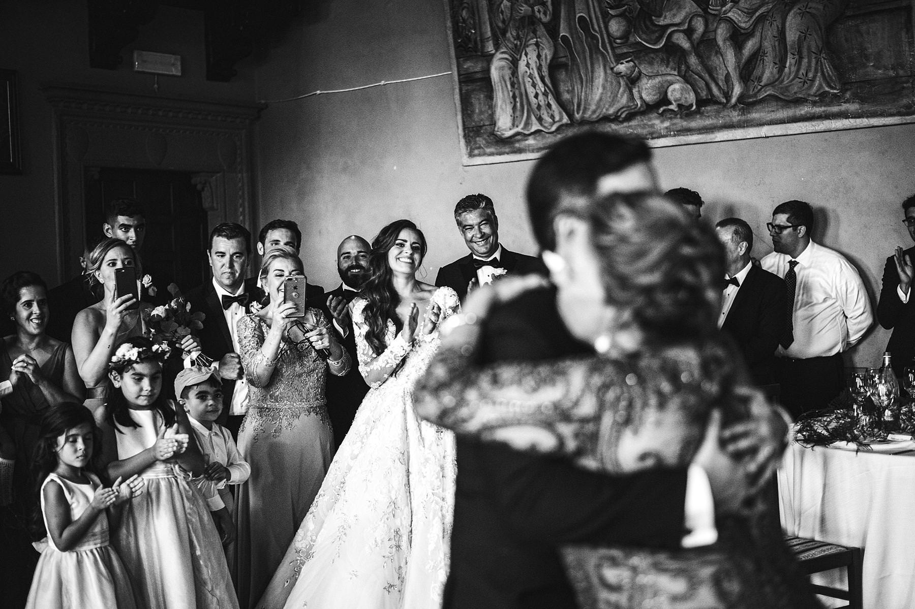 Reportage destination wedding photographer in Tuscany at Valenzano Castle. Groom and mother dance with bride reaction