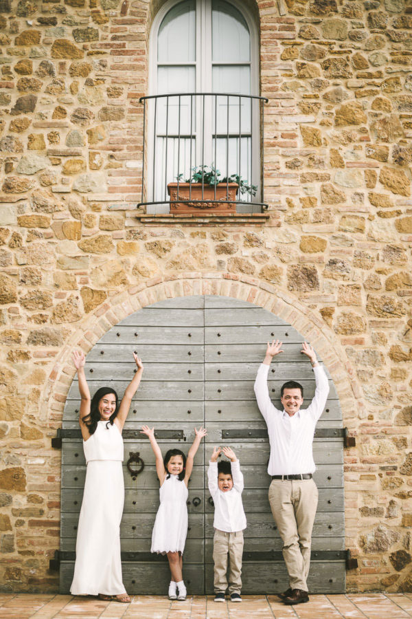 Exciting and fun summer family vacation photo shoot in Tuscany countryside. Mom, dad and kids are enjoying some time during the photo session