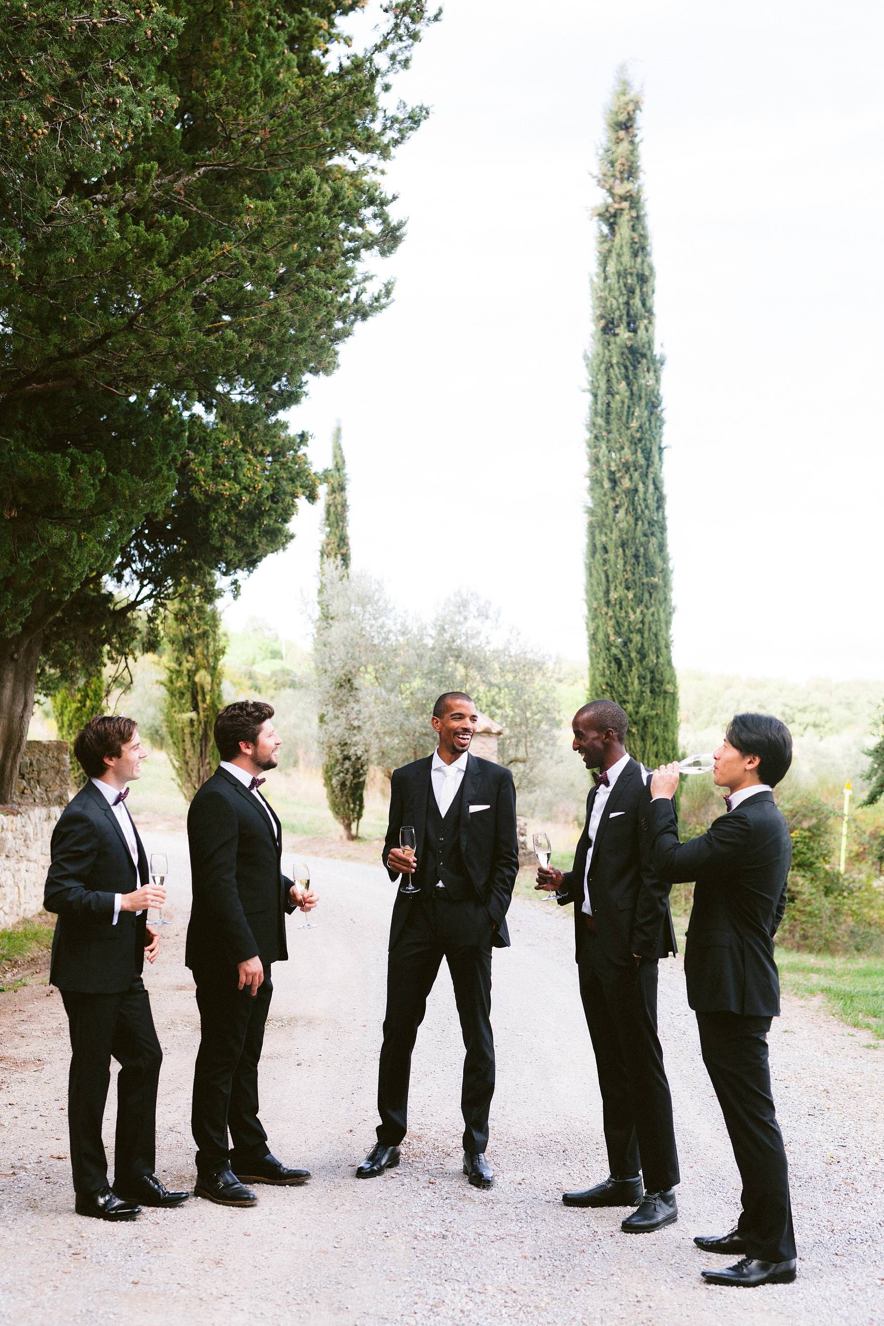 Groom Tanaka with groomsmen wait to walk down the aisle for the symbolic wedding ceremony at charming Montelucci Country Resort historic residence between Chianti and Valdarno framed by the picturesque cypress lane and vineyard
