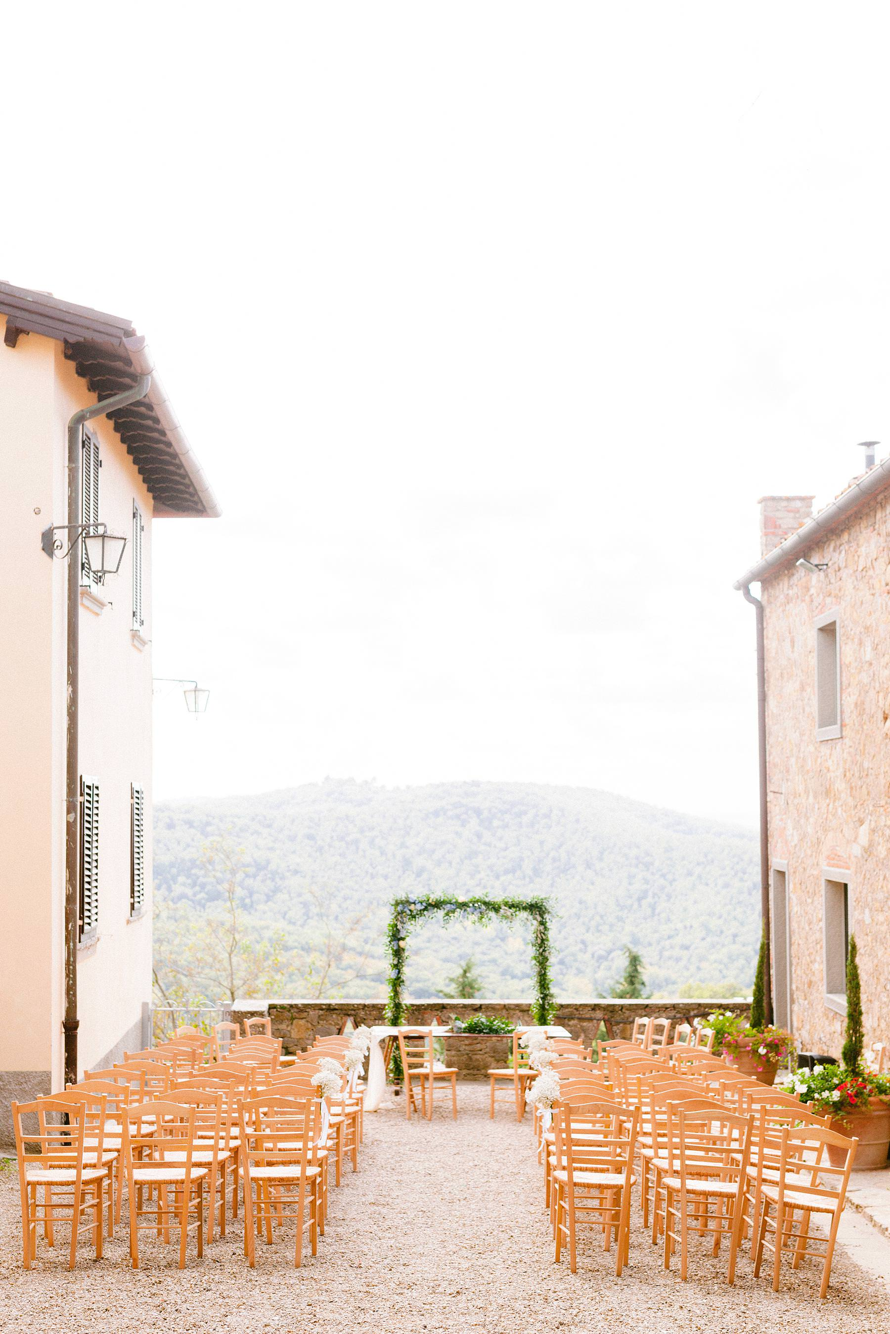 Lovely outdoor wedding ceremony decor at the terrace overlooking the green rolling hills of Tuscany in the charming historic residence of Montelucci Country Resort between Chianti and Valdarno