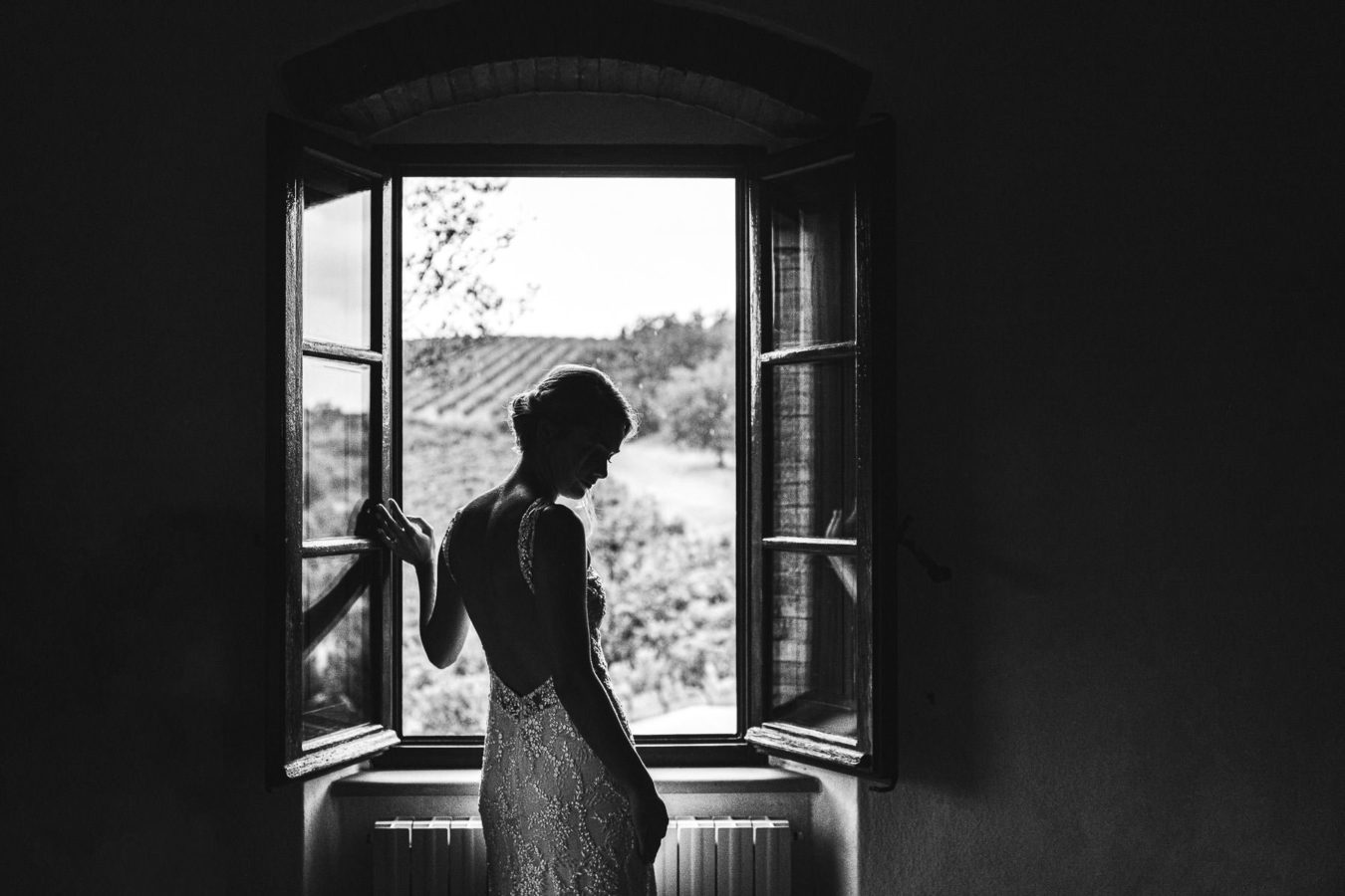 Emotional bride look at the heavy rain outside in her wedding day Le Filigare Tuscany