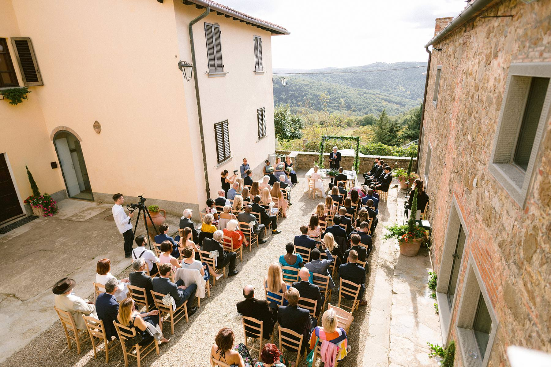 Emotional symbolic outdoor wedding ceremony took on a terrace overlooking the green rolling hills of Tuscany at historic residence of Montelucci Country Resort located between Chianti and Valdarno