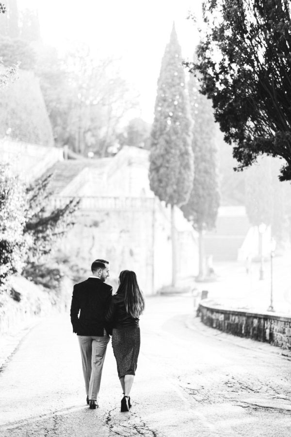 Winter engagement surprise proposal photo shoot Florence. Intimate couple portrait during walk tour in Florence near San Miniato al Monte