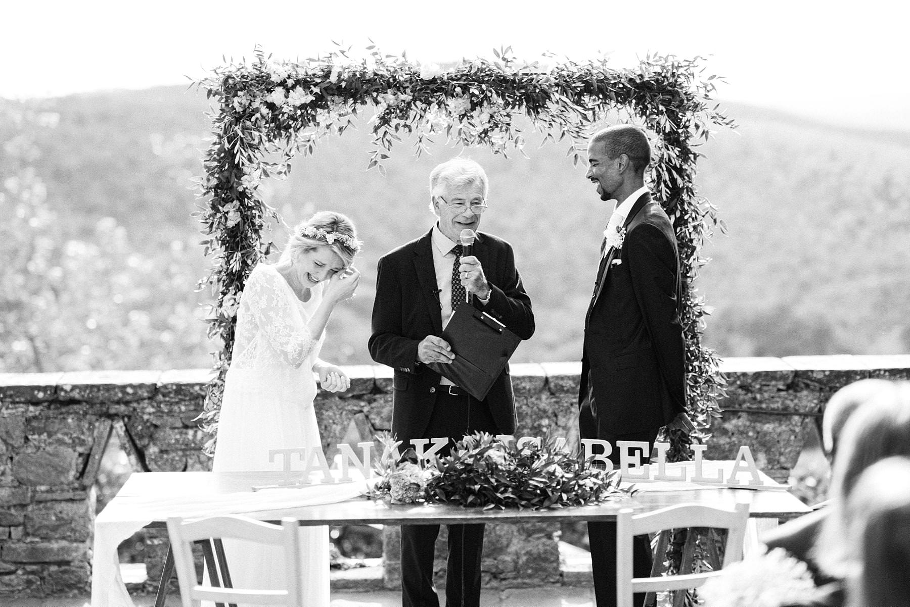 Emotional outdoor symbolic ceremony with exchanging of vowÕs held on a terrace overlooking green rolling hills of Tuscany at historic residence Montelucci Country Resort located between Chianti and Valdarno