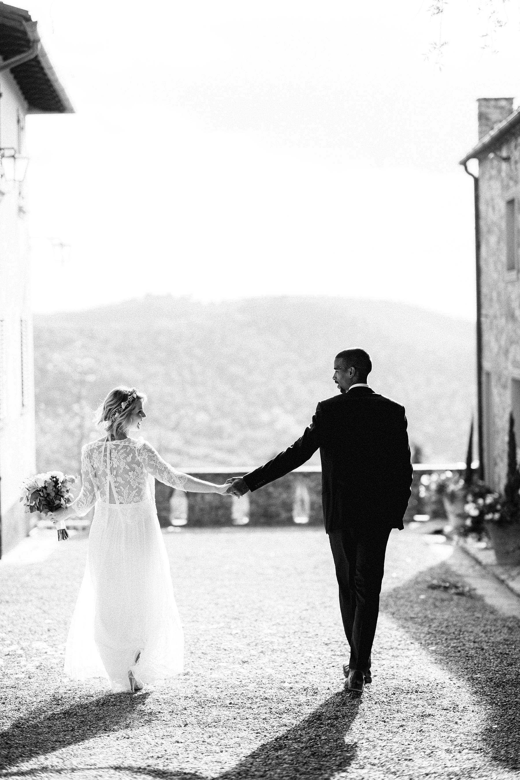 Lovely walk photo tour with bride Isabella in her Laure De Sagazan dress and groom Tanaka in his Hugo Boss suit at the historic residence of Montelucci Country Resort located between Chianti and Valdarno a perfect place for a destination wedding in Tuscany countryside