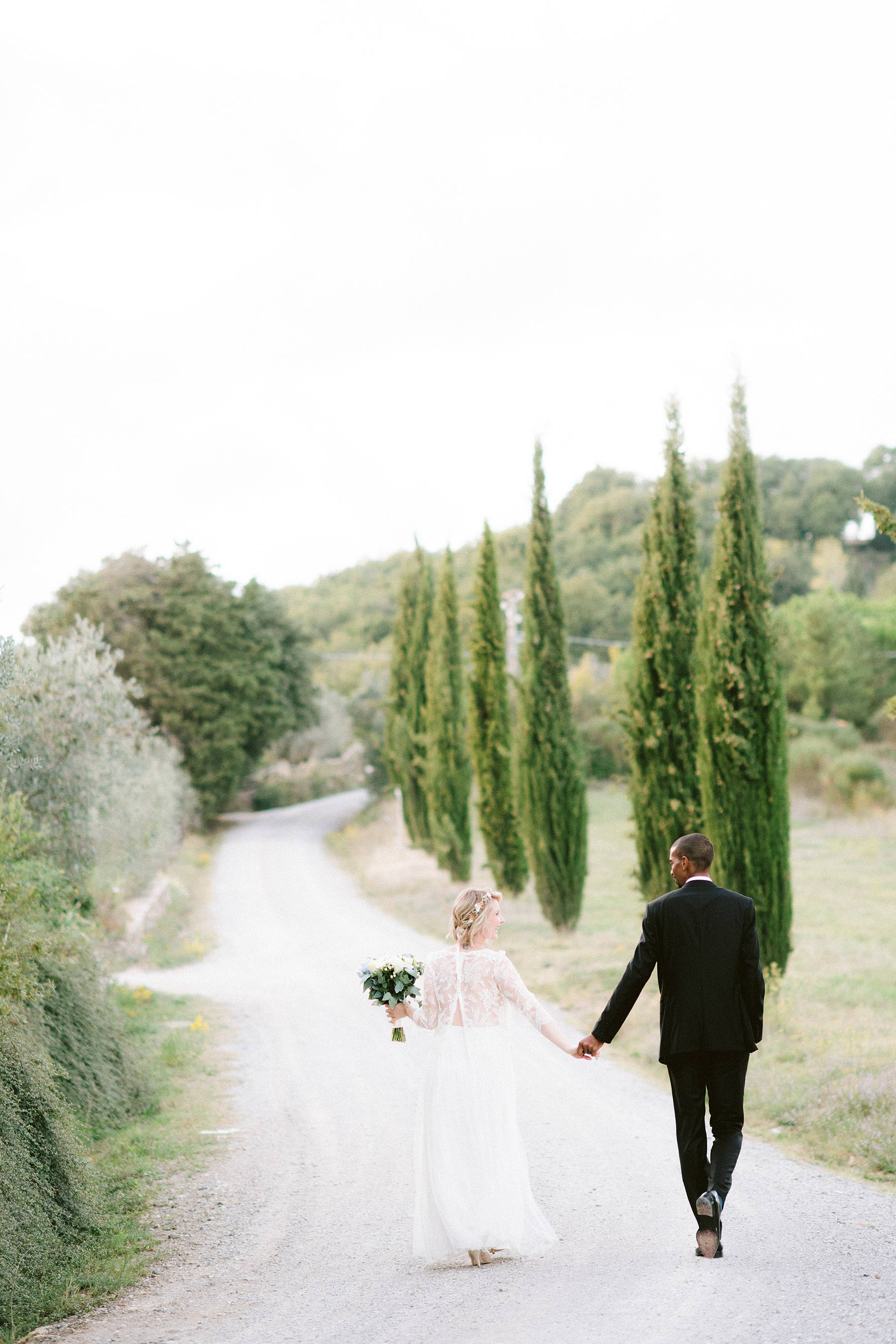 Bride Isabella in her Laure De Sagazan dress and groom Tanaka in his Hugo Boss suit walk around historic residence of Montelucci Country Resort, framed by the picturesque cypress lane and vineyard. Destination wedding in the countryside of Tuscany between Chianti and Valdarno