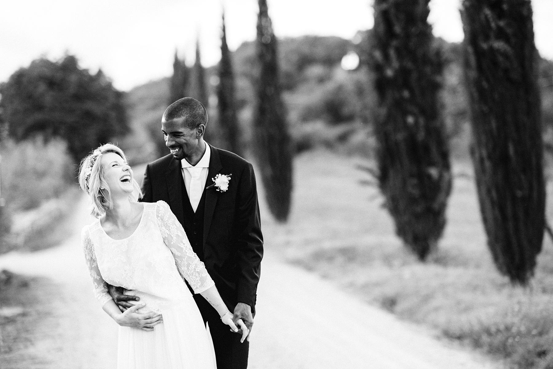Lovely moment between bride Isabella in her Laure De Sagazan dress and groom Tanaka in his Hugo Boss suit during portrait session around historic residence of Montelucci Country Resort, framed by the picturesque cypress lane and vineyard. Destination wedding in the countryside of Tuscany between Chianti and Valdarno