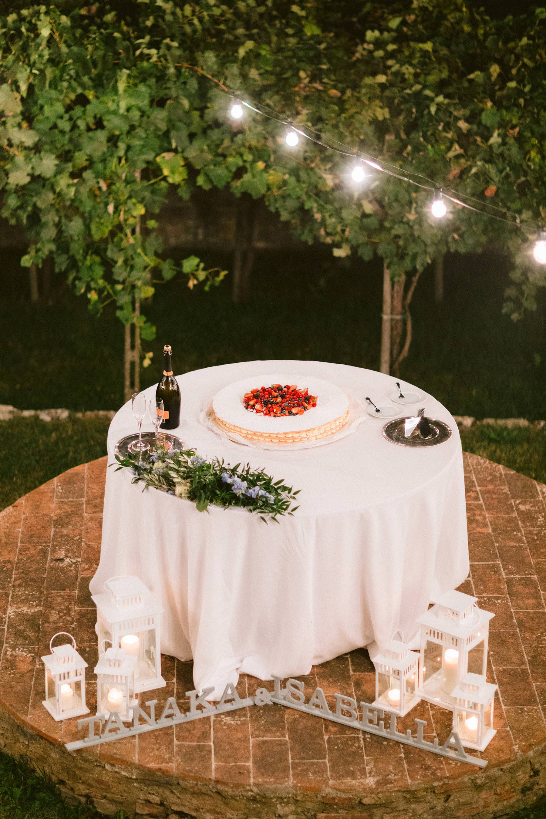 Lovely and delicious cake decor surrounded by lights and sparkles for bride Isabella and groom Tanaka at Montelucci Country Resort in Tuscany countryside