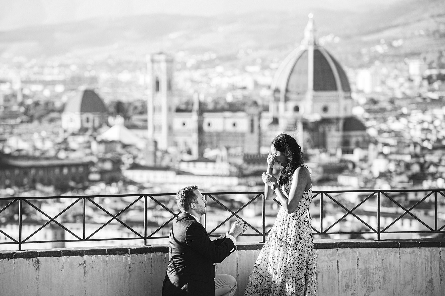 "Angela and Max's surprise marriage proposal photo shoot. Is there anything that speaks of love more than a surprise marriage proposal in Florence, followed by an engagement photoshoot that touches all of its most iconic spots? As a photographer based in this charming city I might be biased, but let me say that it's hard to find anything more romantic than that. When he finally kneeled in front of her – and in front of the most breathtaking panorama of Florence from San Miniato al Monte – it was an intensely emotional moment. A surprise marriage proposal that they will be able to relive over and over again thanks to the photos and short film we realized for them. (And, in case you're wondering, she said ""Yes"".)"