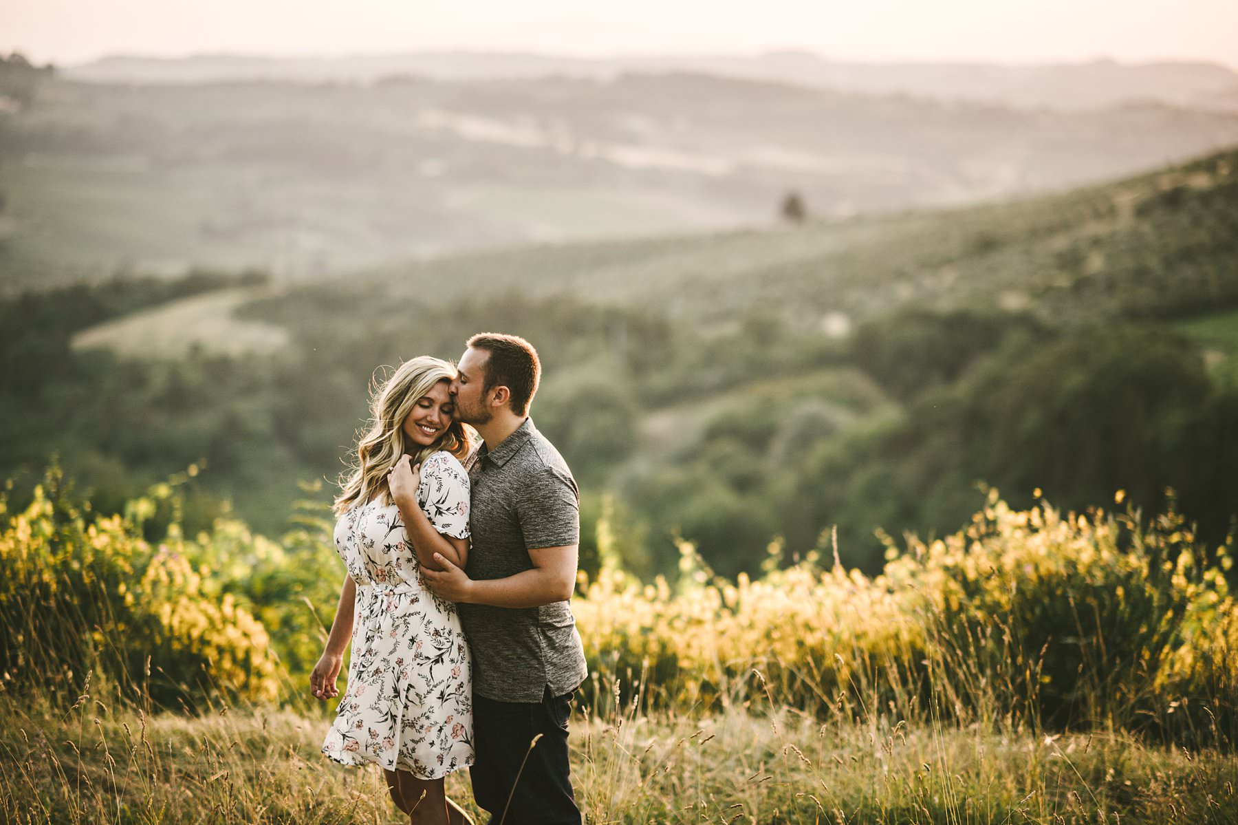 Delicate outdoor engagement photos in Tuscany: a holiday to remember. Discover the magic of Chianti. Outdoor engagement photos in the charming Florence and breathtaking Chianti are the perfect way to celebrate a special and meaningful holiday. The countryside is a sequence of green and gold rolling hills, covered in vineyards and olive groves. A landscape that feels like a fairytale will embrace you while you express your love to each other. Just like Andrea and Aaron who danced, laughed, kissed, hugged and enjoyed every minute of the shooting in such a magical location, caressed by the warm sunset light