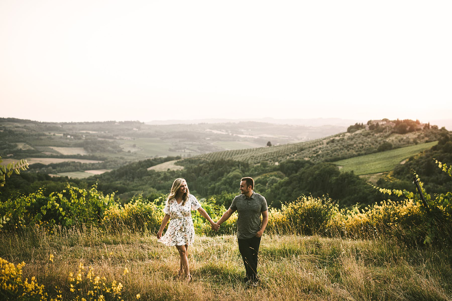 Engagement vacation photo session and discover the magic of Chianti, Tuscany. The countryside is a sequence of green and gold rolling hills, covered in vineyards and olive groves. A landscape that feels like a fairytale will embrace you while you express your love to each other. Just like Andrea and Aaron who danced, laughed, kissed, hugged and enjoyed every minute of the shooting in such a magical location, caressed by the warm sunset light.