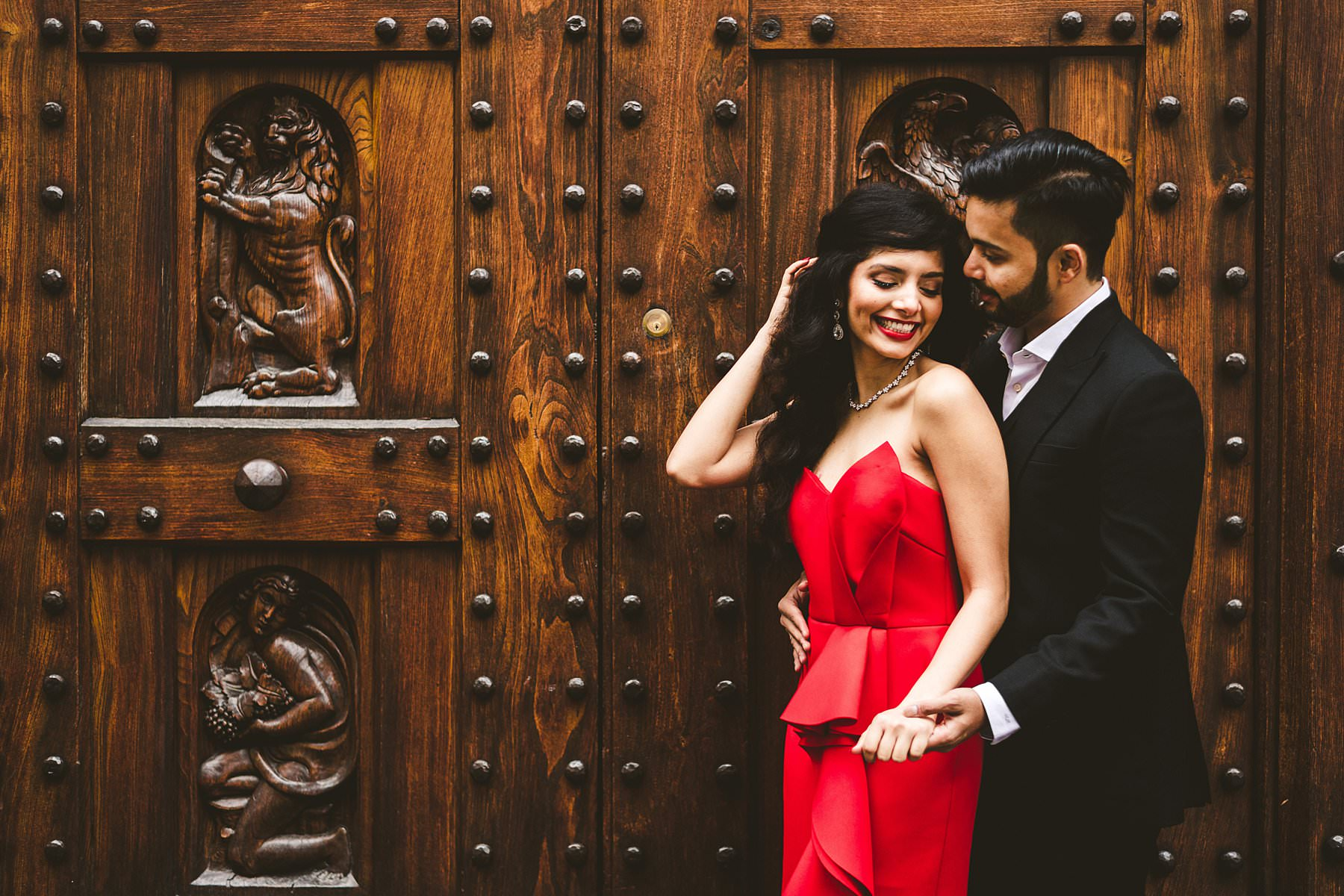 Stunning engagement couple portrait in Florence with the ancient historic door near Piazza del Duomo in the heart of the city