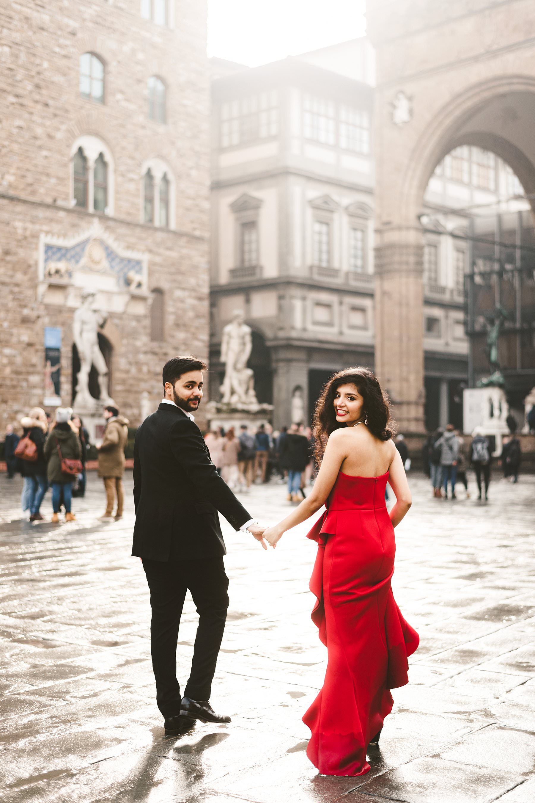 The magic of winter engagement photos. If Florence in winter wasn't perfect itself as a destination engagement setting, Pryia definitely contributed to making it even more fascinating thanks to the stunning red dress she wore during the shooting. She lit up that foggy day and the eyes of every passer-by were on her. We started taking their destination engagement photos at the Duomo, with its white-and-green marble geometry as a background, then walked all over the heart of the city. Piazza della Signoria, Uffizi Gallery, Ponte Vecchio, Via de' Tornabuoni: Pryia and Sid floated around, unconcerned by the cold temperature and focused only on their love