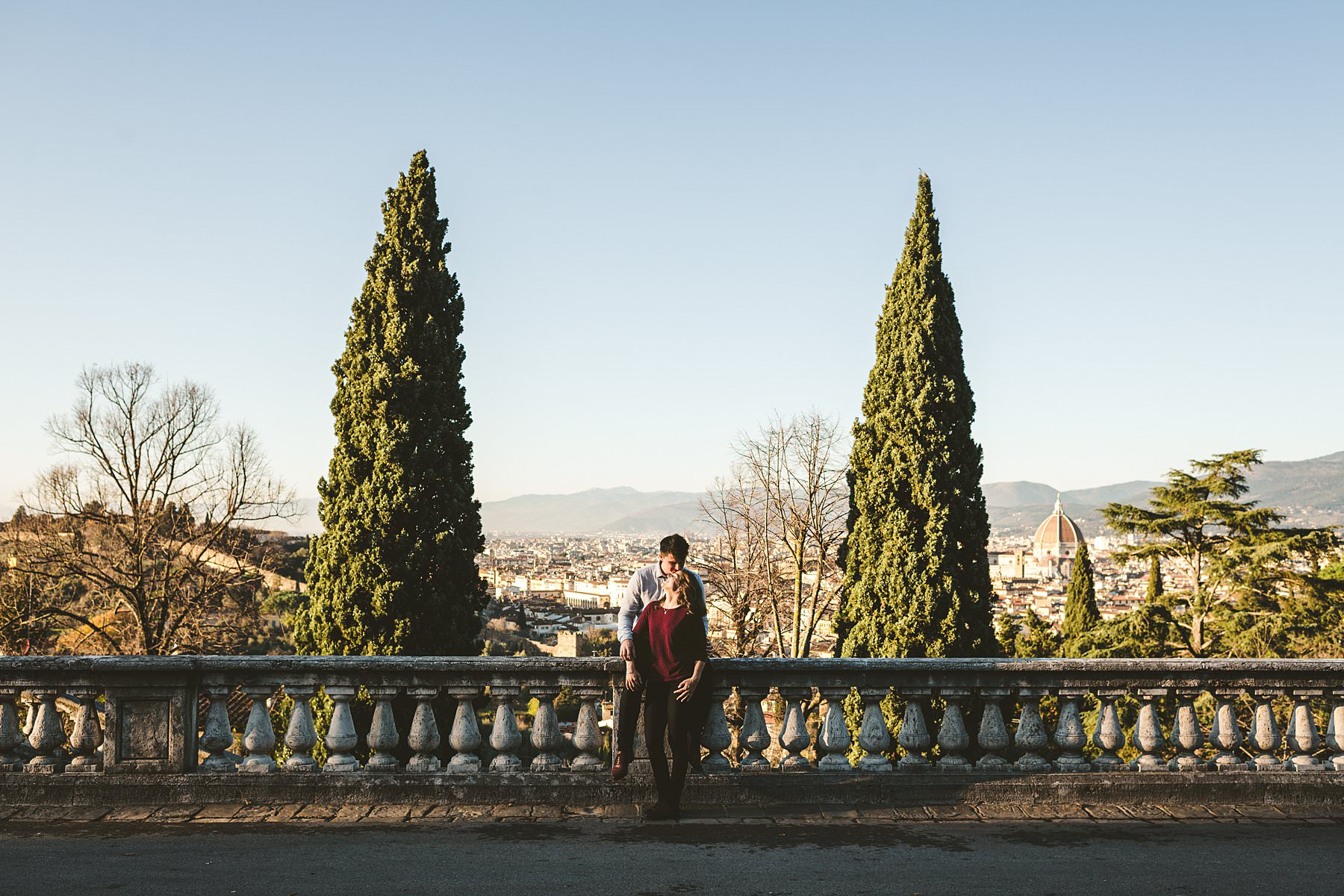 The charm of Florence in winter. Even though it was winter, due to the Christmas holidays Florence was crowded with tourists, and the day we picked for these romantic engagement photos – December 23rd – was no exception. This is one of the reasons why our session started in San Miniato al Monte: besides offering a breathtaking view of the city and many different backgrounds to play with, it's usually less busy than other spots. It's no surprise that it turned out to be perfect to break the ice with Claudia and Andrew, who then could feel free to express their love to one another with hugs, kisses and heartfelt smiles