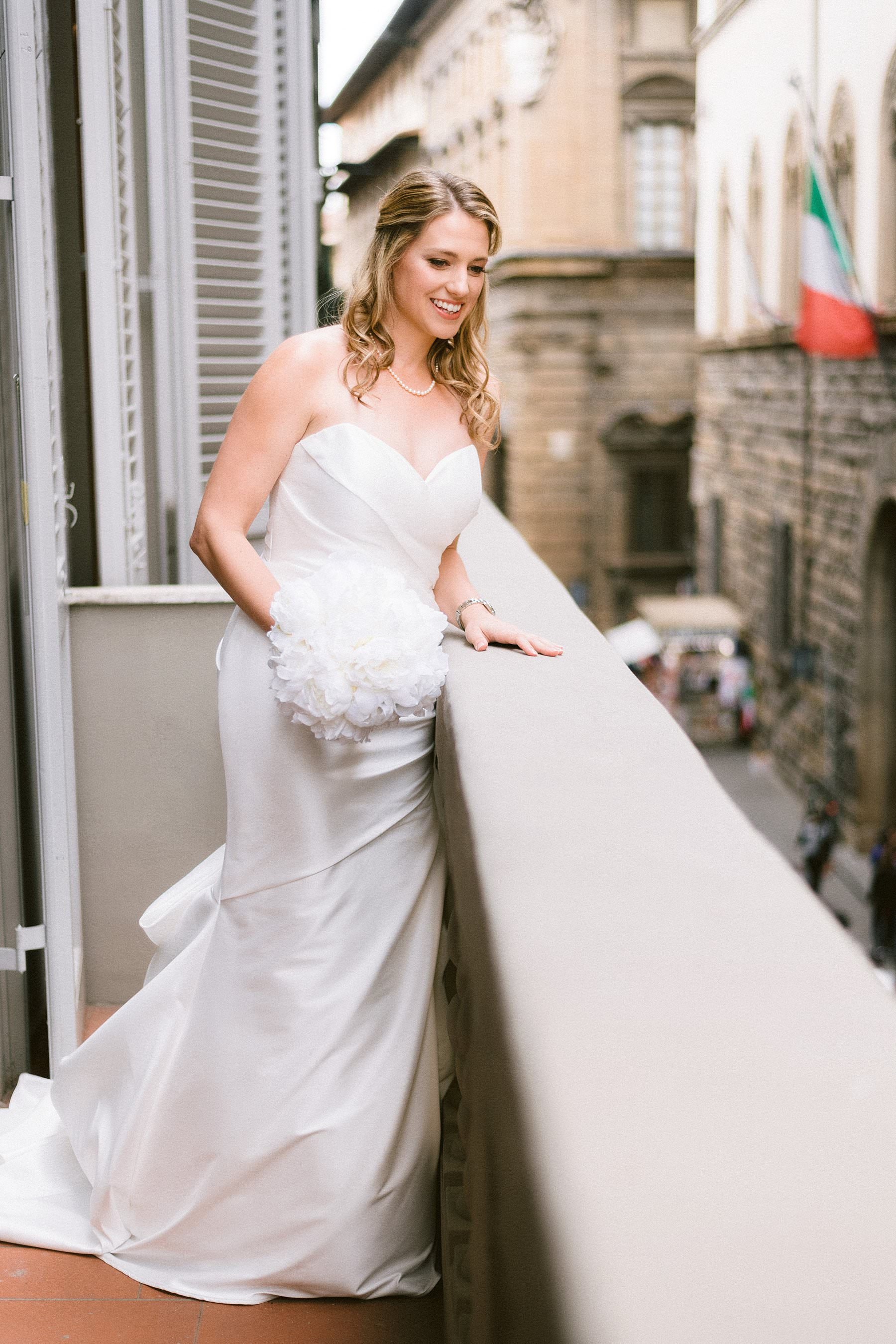 Intimate exquisite wedding in the heart of Florence, Italy. Lovely, smiling and elegant bride Beth is almost ready to leave Grand Hotel Cavour suite for the destination wedding ceremony