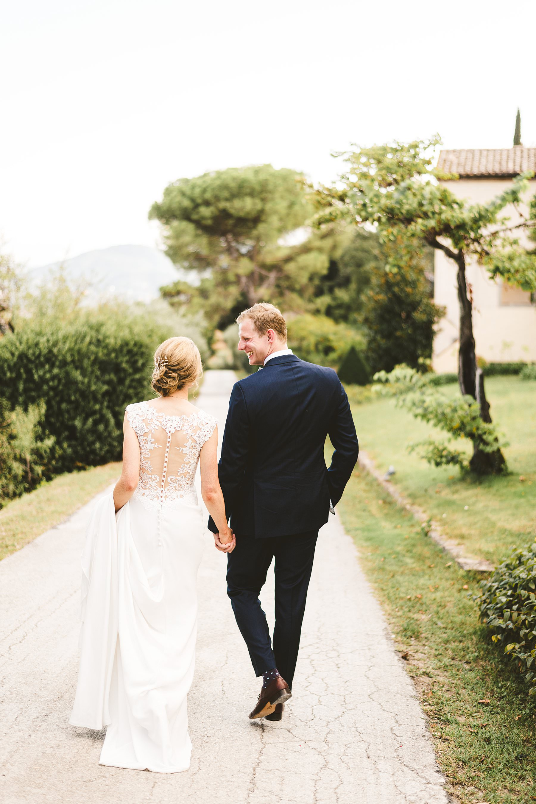 A special international wedding in the countryside of Umbria, Italy. Elegant Australian wedding couple portrait around the property of Villa Monte Solare, a historic residence tucked in the countryside among rolling hills. The settings were countryside landscapes with cypress lines, olive groves and a stunning wall covered in red ivy leaves